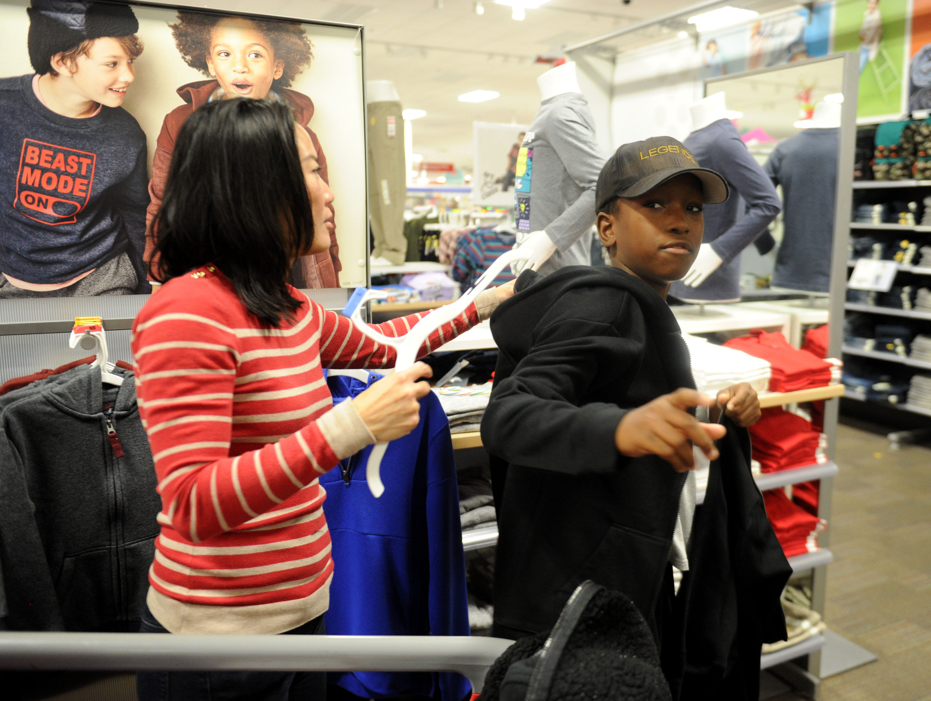 Kristina Tansavatdi, with the Rotary Club of Westlake Village, helps Samuel Opoku gets a hoodie and a gift for his mom. The club hosted a shopping spree at Target for 36 members of the Boys & Girls Club. The children, each with $110 to spend, were paired with 36 volunteers, and they also got two $10 gift cards so they could buy gifts for someone else.