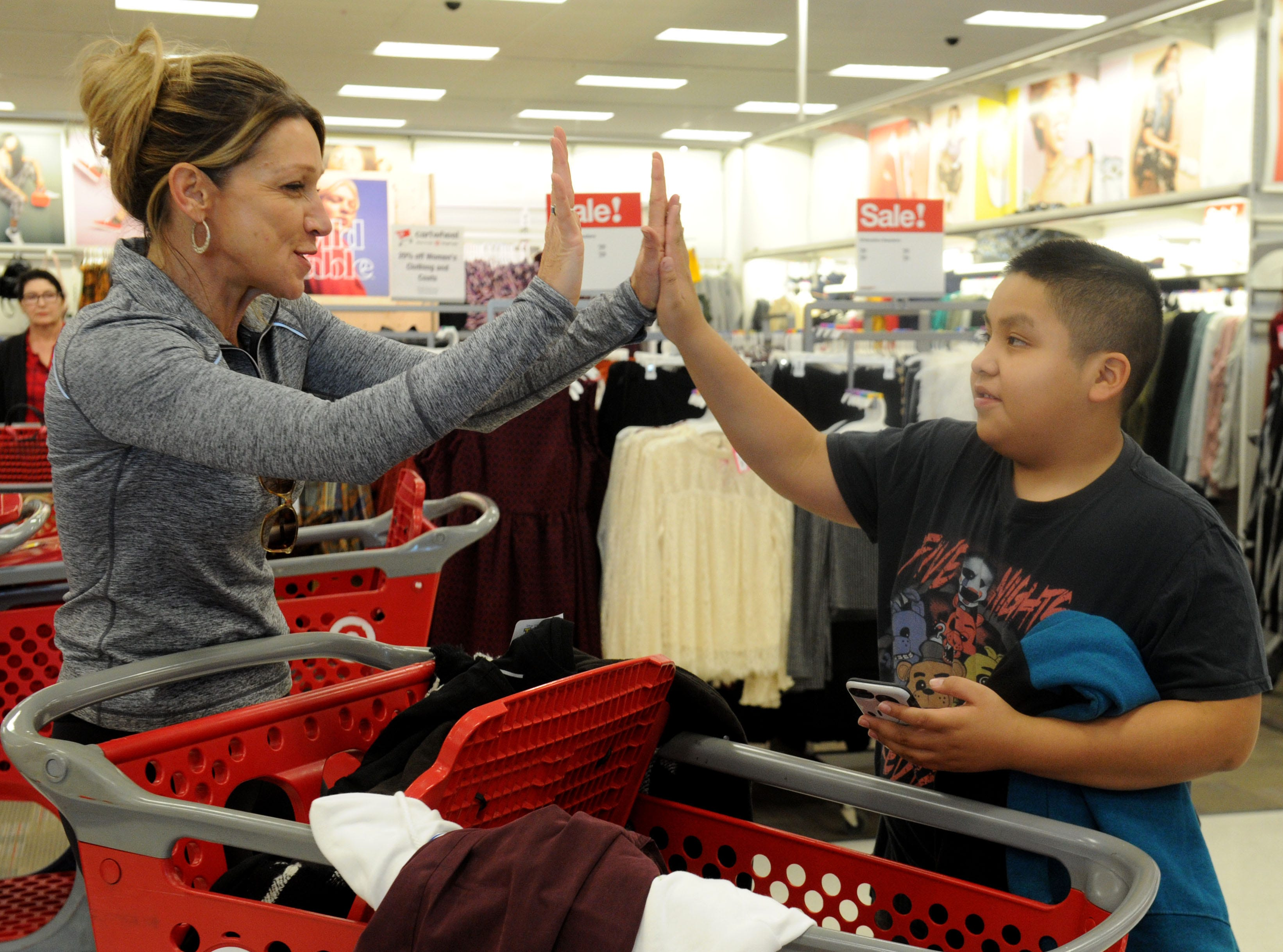 Erin Culbertson, with the Rotary Club of Westlake Village, celebrates with Roberto Aldana after helping him select clothes and Christmas gifts for him and his family. The club hosted a shopping spree at Target for 36 members of the Boys & Girls Club. The children, each with $110 to spend, were paired with 36 volunteers, and they also got two $10 gift cards so they could buy gifts for someone else.