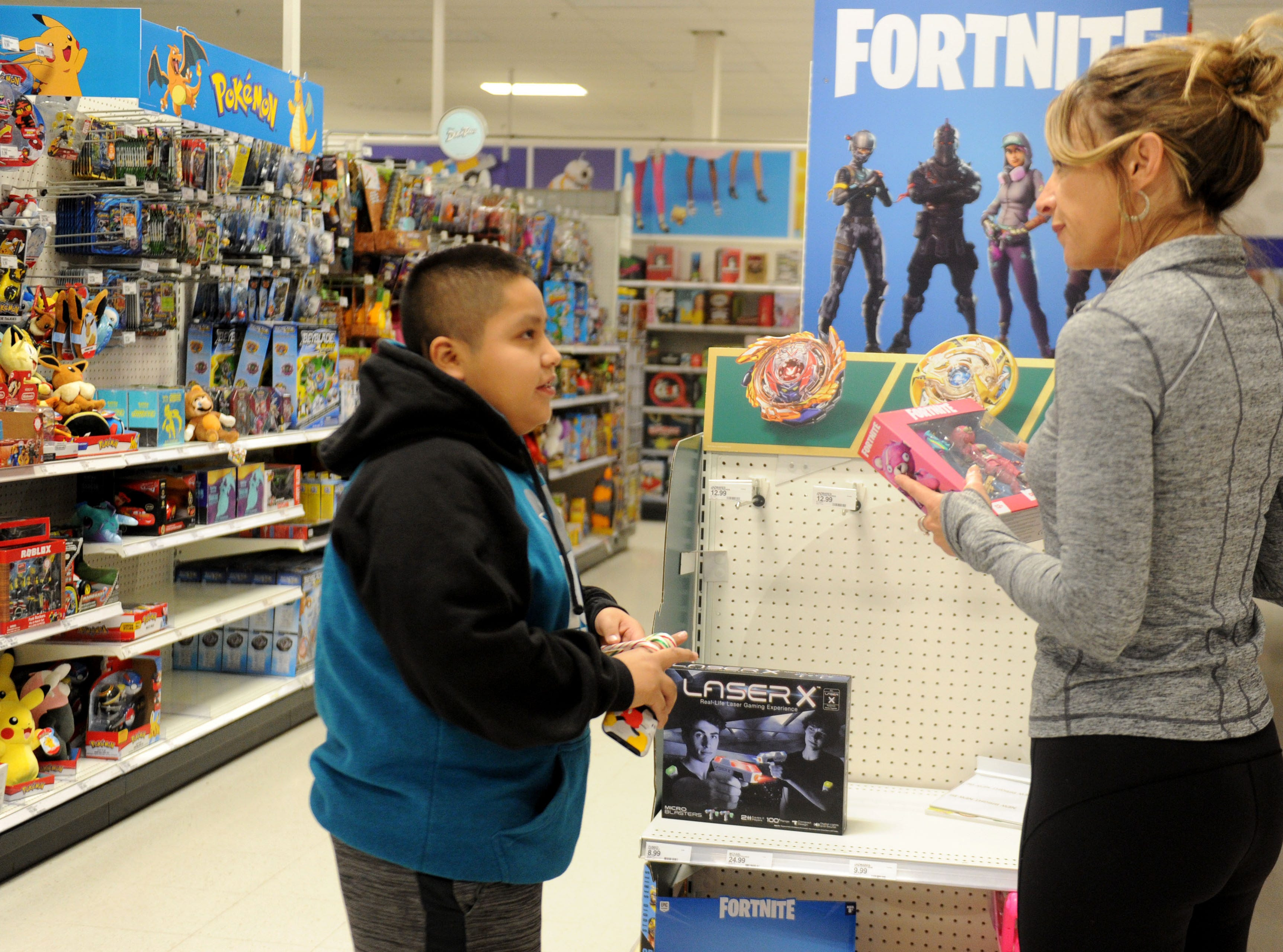 Erin Culbertson, with the Rotary Club of Westlake Village, helps Roberto Aldana shop for toys and Christmas gifts for him and his family. The club hosted a shopping spree at Target for 36 members of the Boys & Girls Club. The children, each with $110 to spend, were paired with 36 volunteers, and they also got two $10 gift cards so they could buy gifts for someone else.