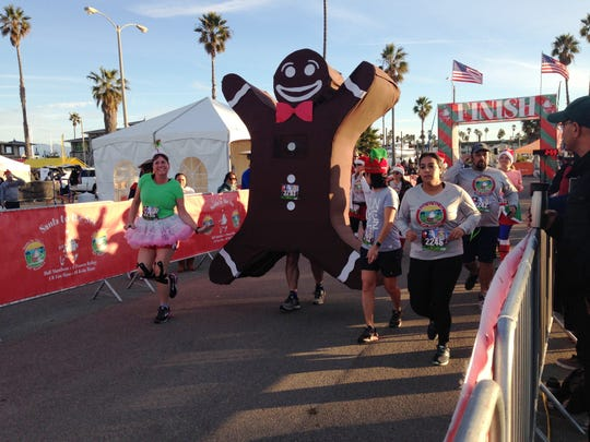 A runner dressed as a gingerbread man joins the 2018 Santa to the Sea race in Oxnard.