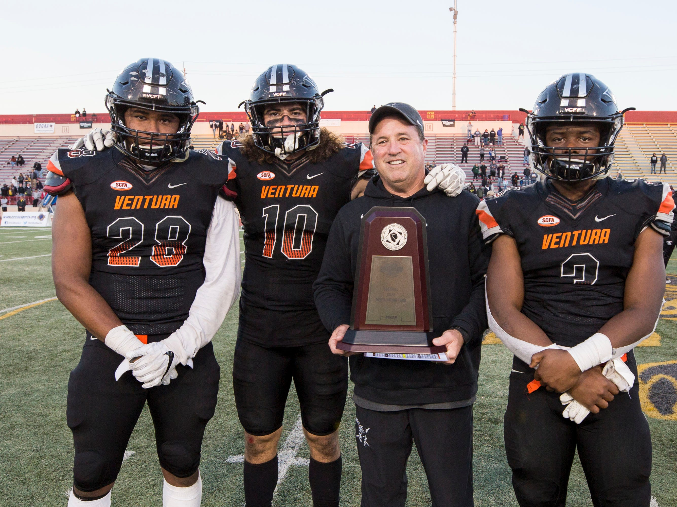 Ventura College head coach Steve Mooshagian poses with the CCCAA state finalist trophy alongside captains Dondre Baker (28), Trennan Carlson (10) and Thomas Duckett (3) after  the CCCAA state championship game on Saturday afternoon at Sacramento City's Hughes Stadium. Laney won, 40-35.