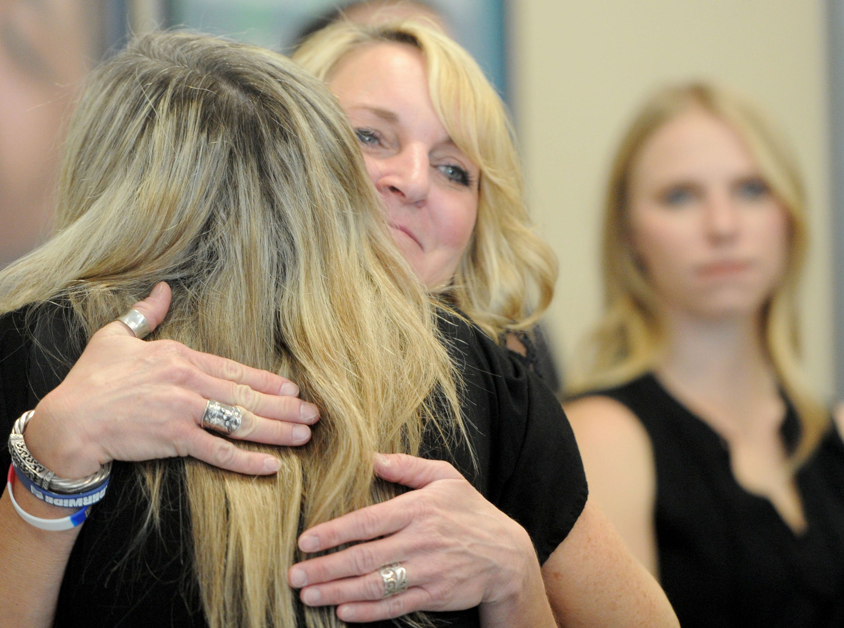 Kathy Dunham gets hugs from friends and family members at the start of the memorial service for her son Jake Dunham, one of those killed the night of Nov. 7 at the Borderline Bar & Grill in Thousand Oaks