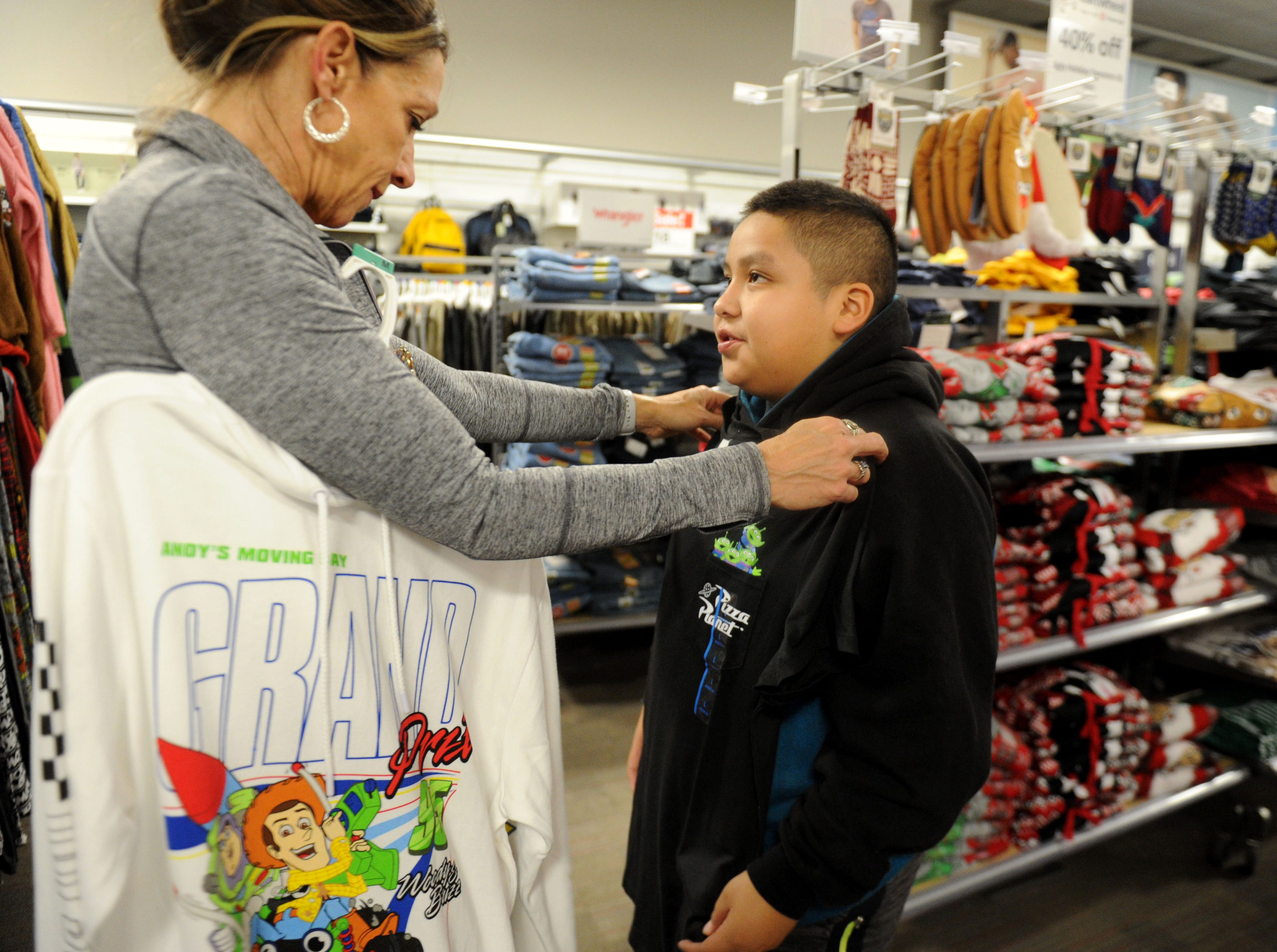 Erin Culbertson, with the Rotary Club of Westlake Village, helps Roberto Aldana shop for Christmas gifts for him and his family. The club hosted a shopping spree at Target for 36 members of the Boys & Girls Club. The children, each with $110 to spend, were paired with 36 volunteers, and they also got two $10 gift cards so they could buy gifts for someone else.