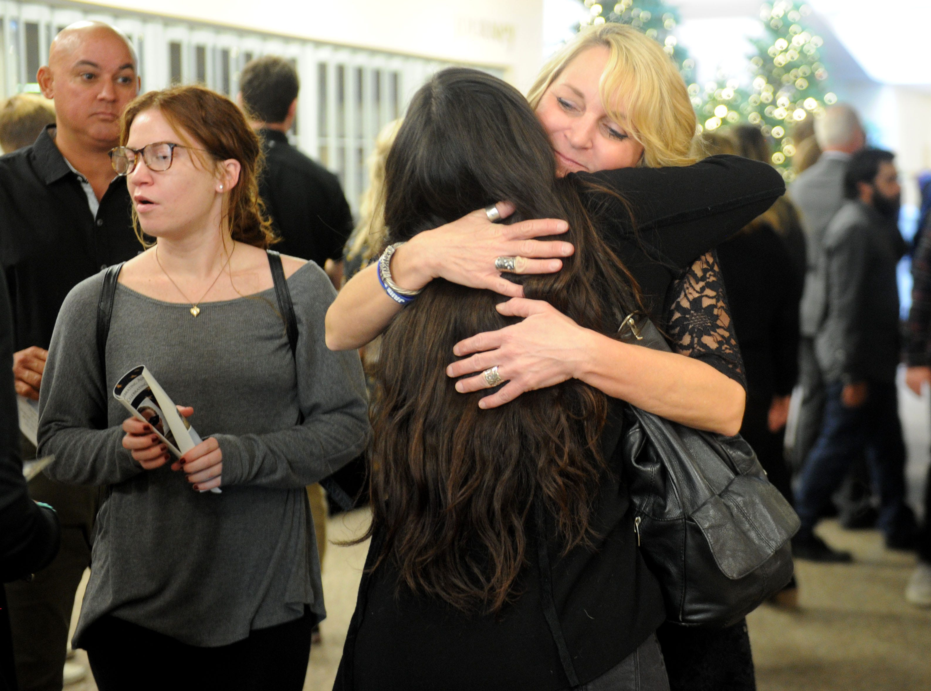 Kathy Dunham gets hugs from friends and family members at the start of the memorial service for her son Jake Dunham, one of those slain the night of Nov. 7 at the Borderline Bar & Grill in Thousand Oaks.