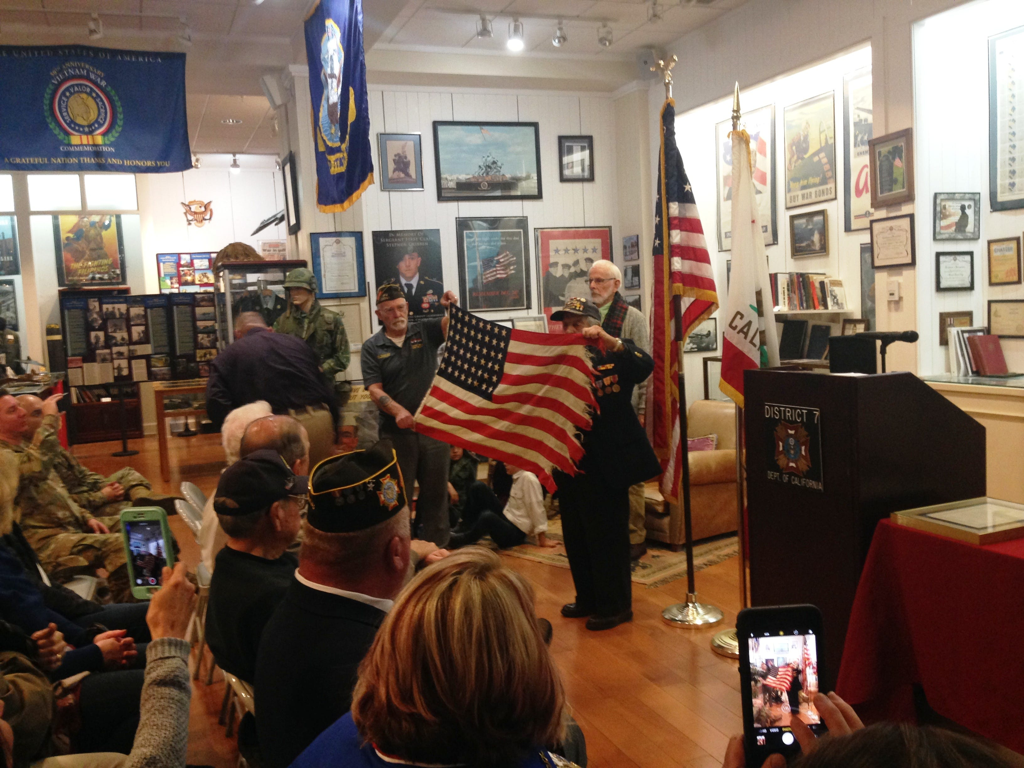 Barney P. Leone, a 94-year-old veteran of World War II who served aboard the USS Nemasket, shows the flag that was flying aboard his ship when he was in the Navy. Leone was a guest speaker at a commemoration of the 77th anniversary of the attack at Pearl Harbor, Hawaii. The event took place at the VFW Museum of Military History in Simi Valley on Dec. 7.