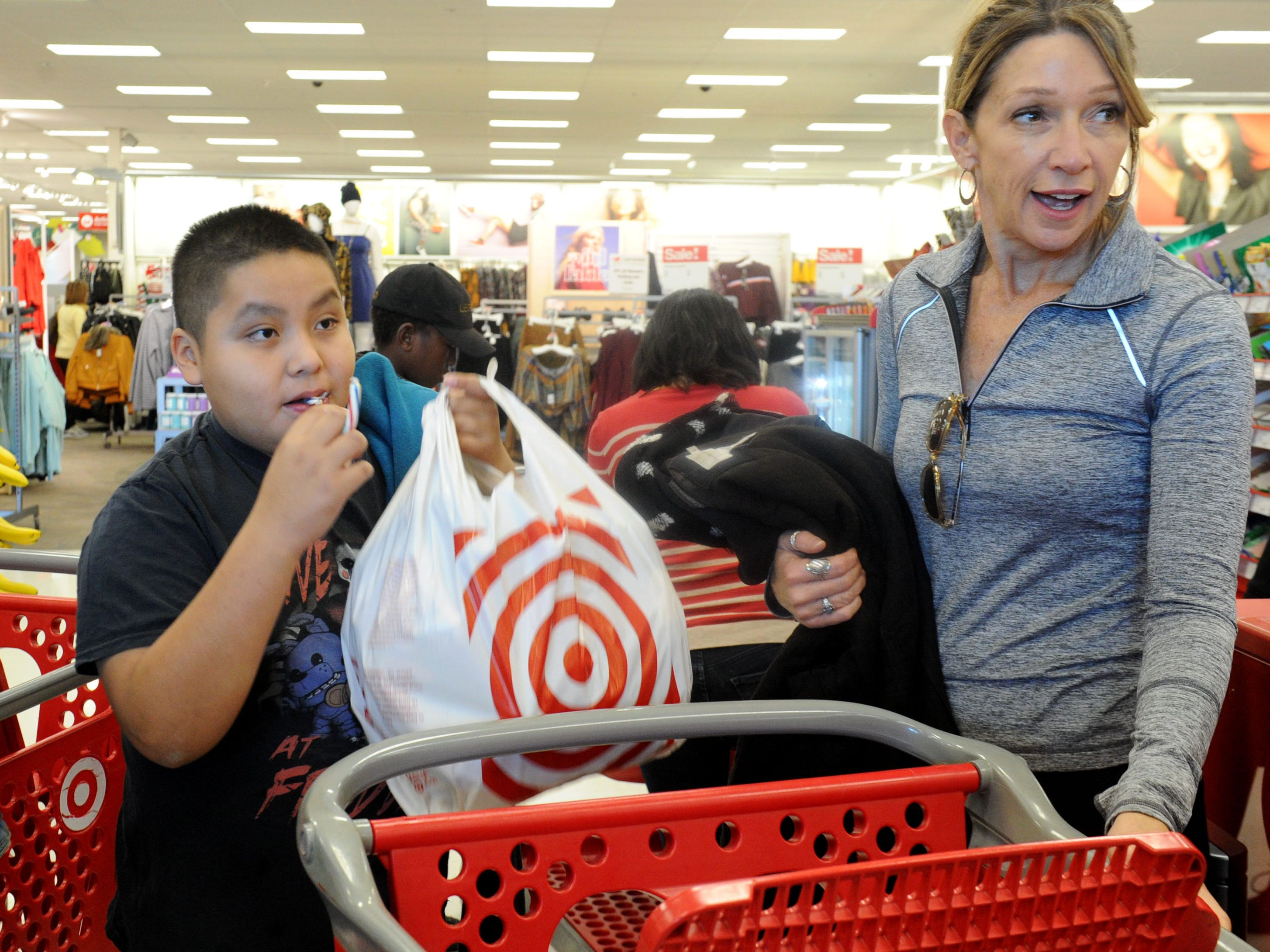 Erin Culbertson, with the Rotary Club of Westlake Village, finishes shopping with Roberto Aldana. The club hosted a shopping spree at Target for 36 members of the Boys & Girls Club. The children, each with $110 to spend, were paired with 36 volunteers, and they also got two $10 gift cards so they could buy gifts for someone else.