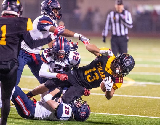 San Joaquin Memorial defenders Will Jacobs (13), Daniel Flores and Joshua Kelly pull down Tulare Union's Julian Espinoza (13) in a CIF State Northern California Division 2-A Regional Bowl Game on Saturday, December 8, 2018.