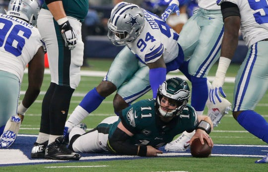 Philadelphia Eagles quarterback Carson Wentz (11) is sacked by Dallas Cowboys defensive end Randy Gregory (94) during the first half of an NFL football game, in Arlington, Texas, Sunday, Dec. 9, 2018. (AP Photo/Michael Ainsworth)