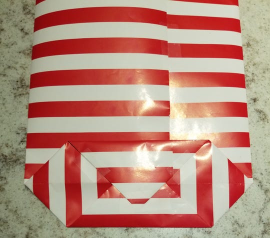 Making your own gift bag, Step 4: Fold the bottom point up to the center and tape.  Fold the top point down to meet the other point, overlapping a bit and tape the seams. Gently slide your hand inside the bag and unfold the bottom and stand the bag up.
