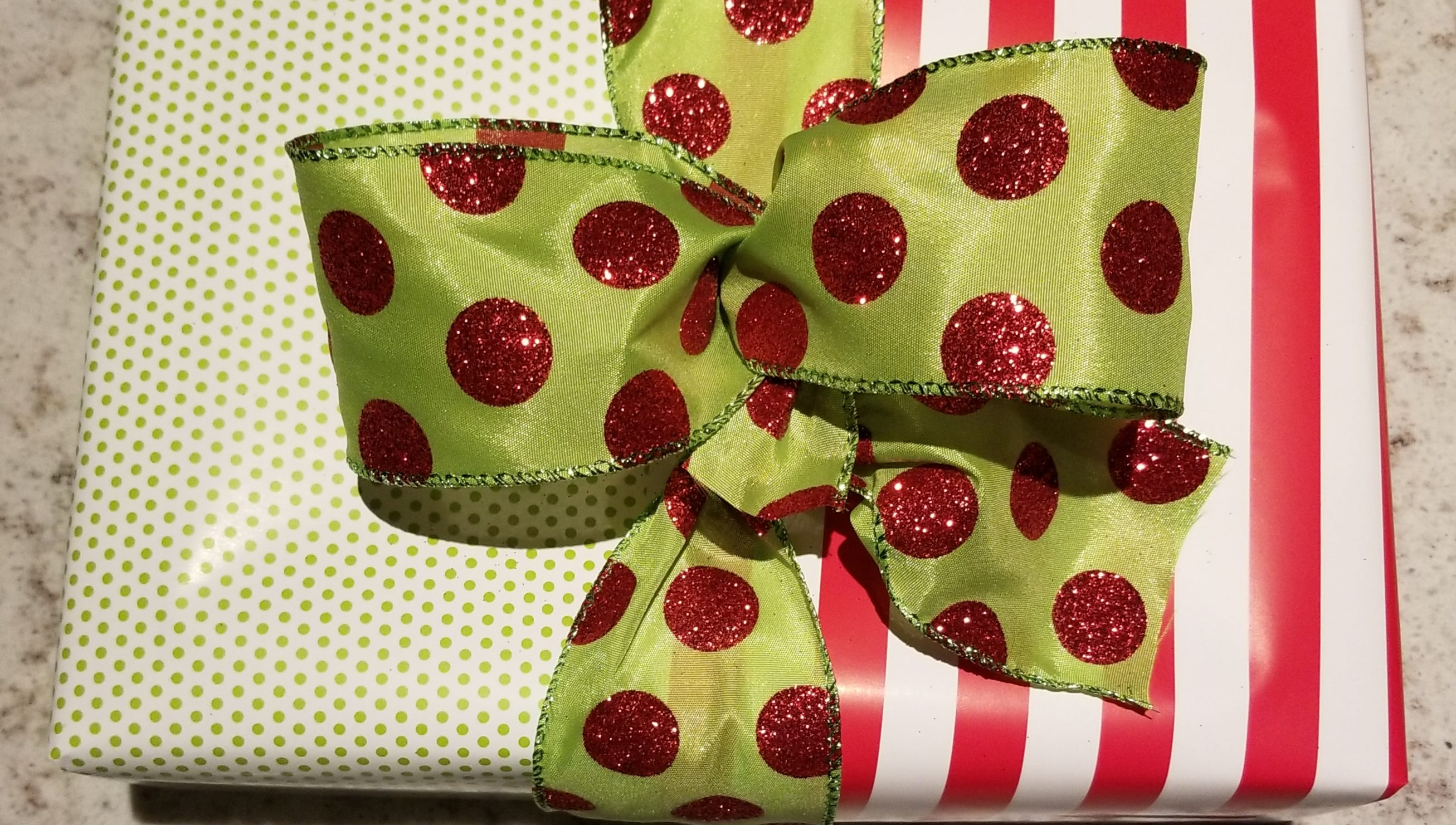 Use different patterns of wrapping paper for a unique look. Wrap each end of the gift with each of the pieces of paper, place a pretty ribbon over the seam to cover it and tie in a bow.