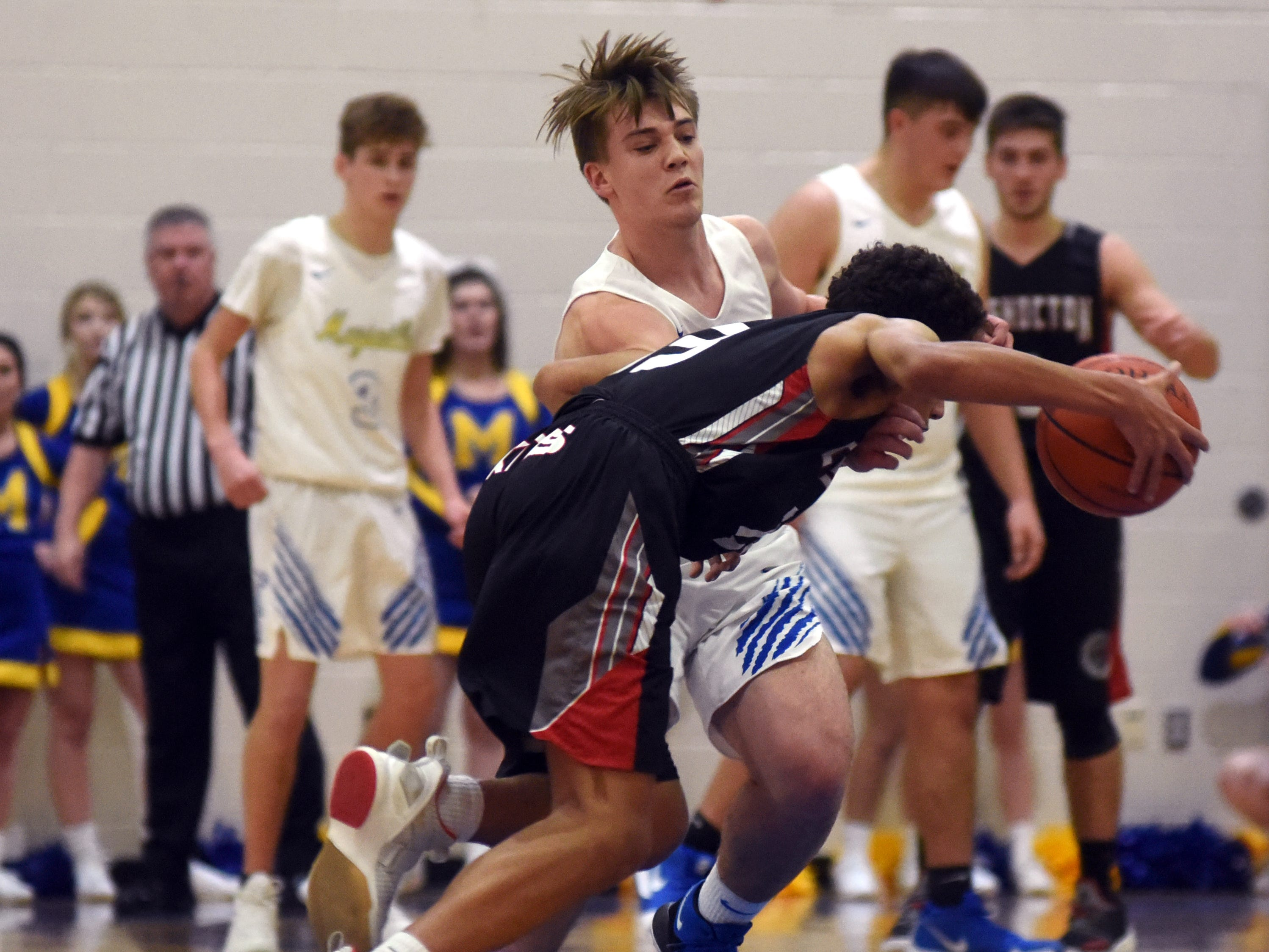 Coshocton's Tyren Walker is guarded closely by Maysville's Kaiden Hall on Saturday night in Newton Township.