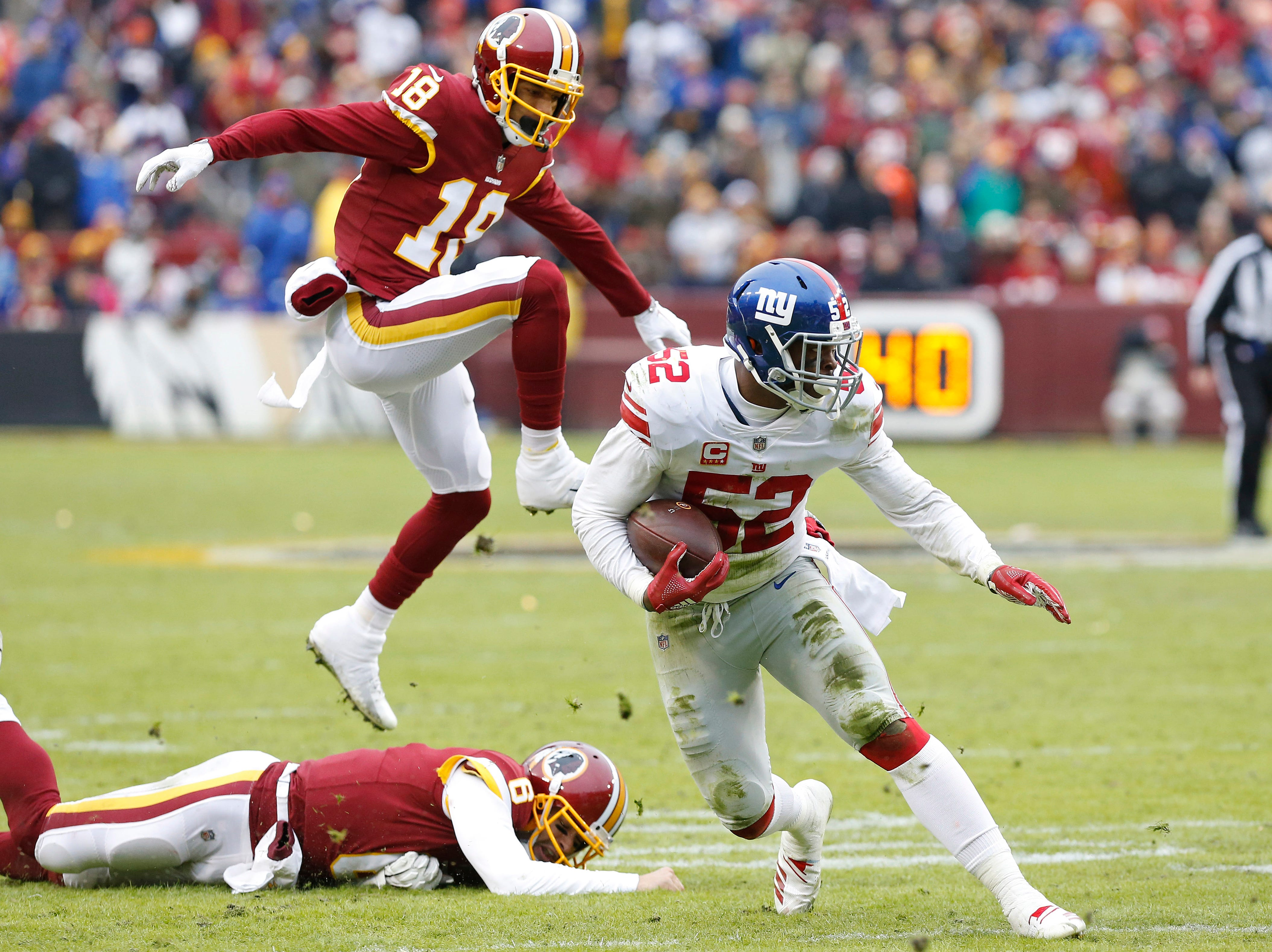 Giants linebacker Alec Ogletree runs with the ball after intercepting a pass by Redskins quarterback Mark Sanchez.