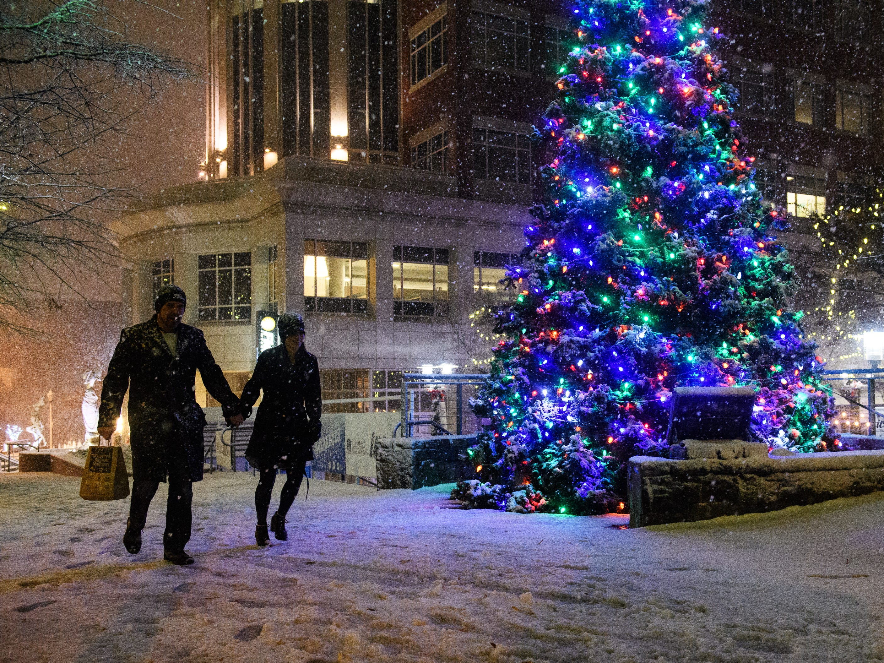 Chad and Shannan Ackerman walk down Main Street as snow begins to fall in Greenville, S.C., Sunday, Dec. 9, 2018.