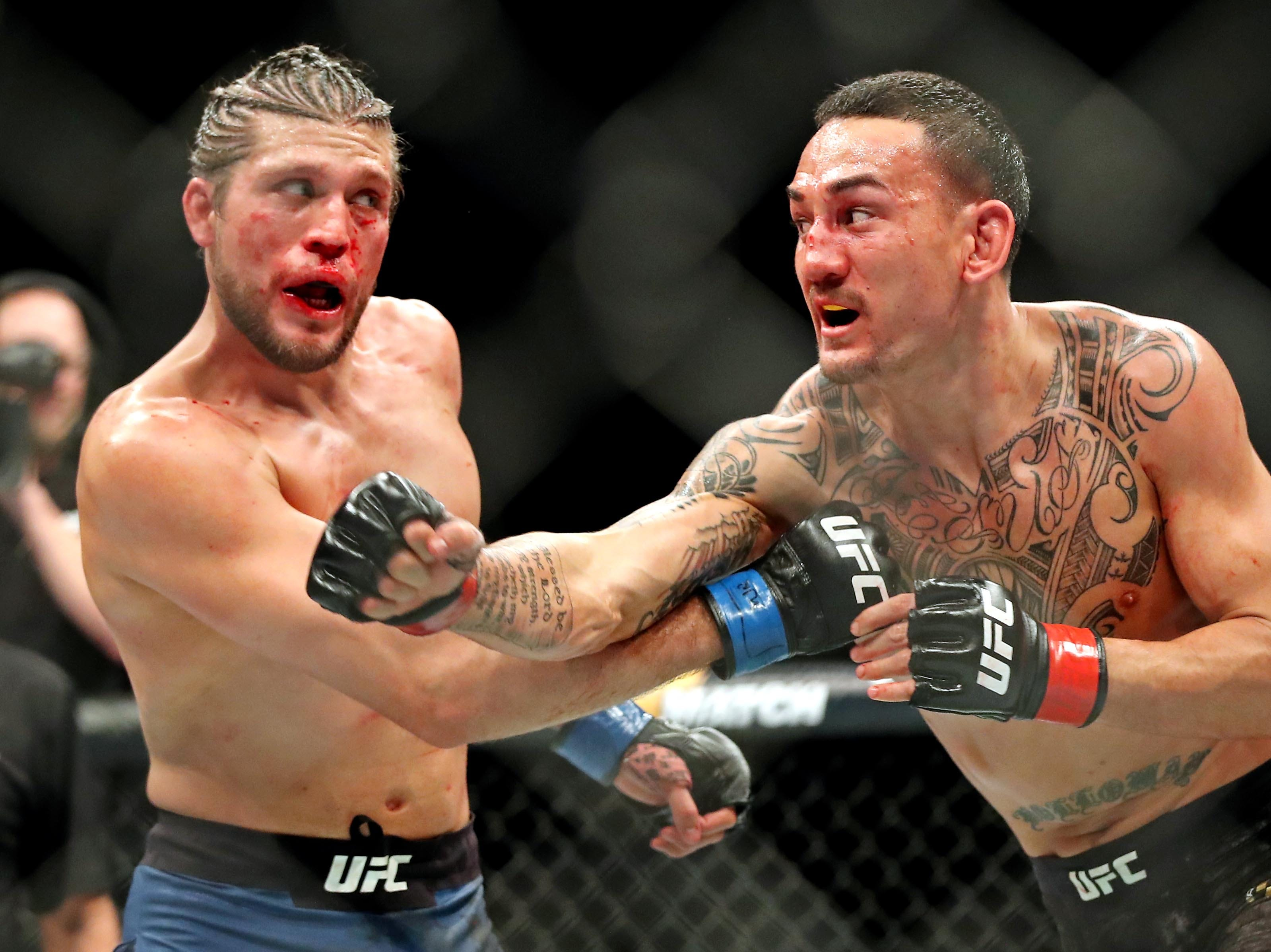 Max Holloway (red gloves) fights Brian Ortega (blue gloves) during UFC 231 at Scotiabank Arena.