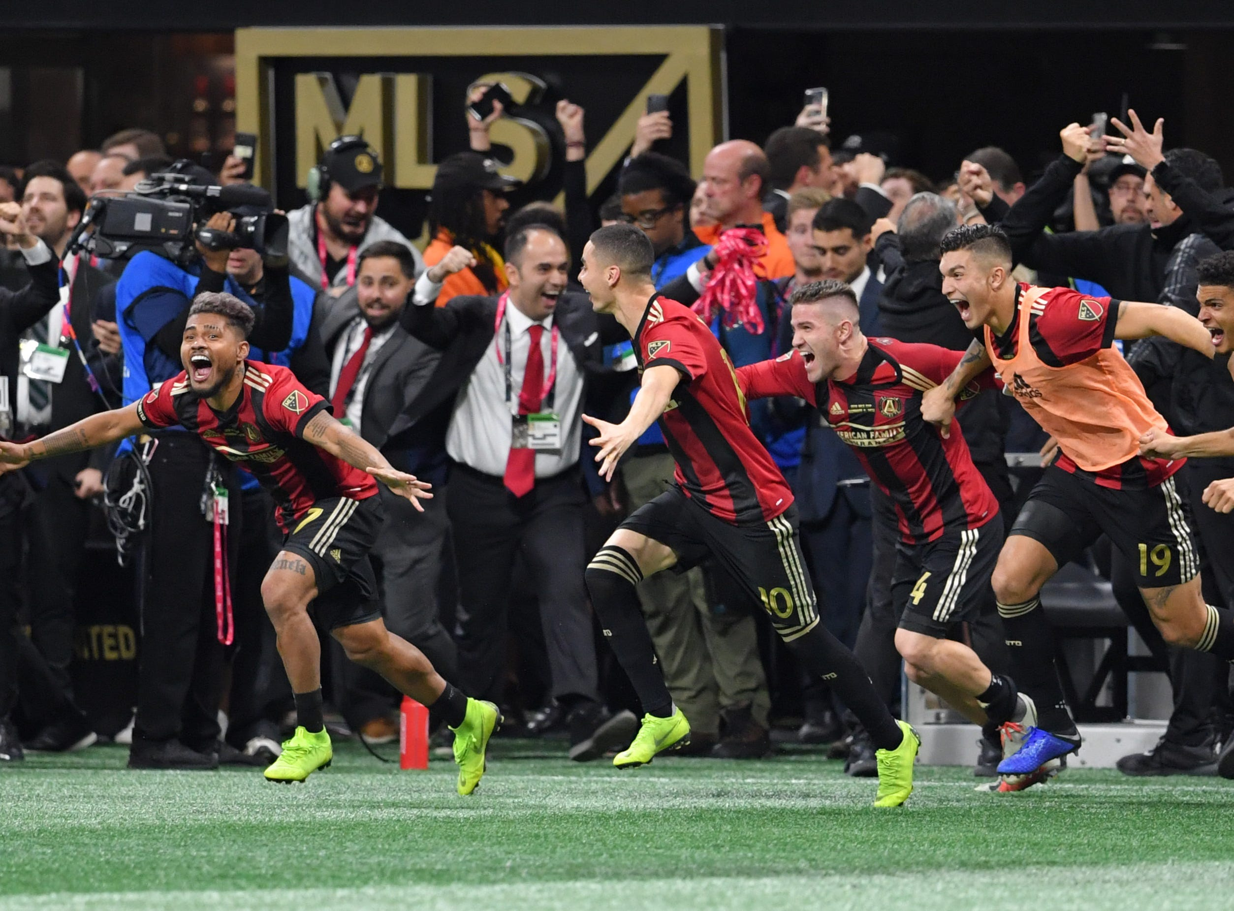 Atlanta United forward Josef Martinez (7) and his teammates rush the field after defeating the Portland Timbers 2-0 in the 2018 MLS Cup championship game at Mercedes-Benz Stadium.