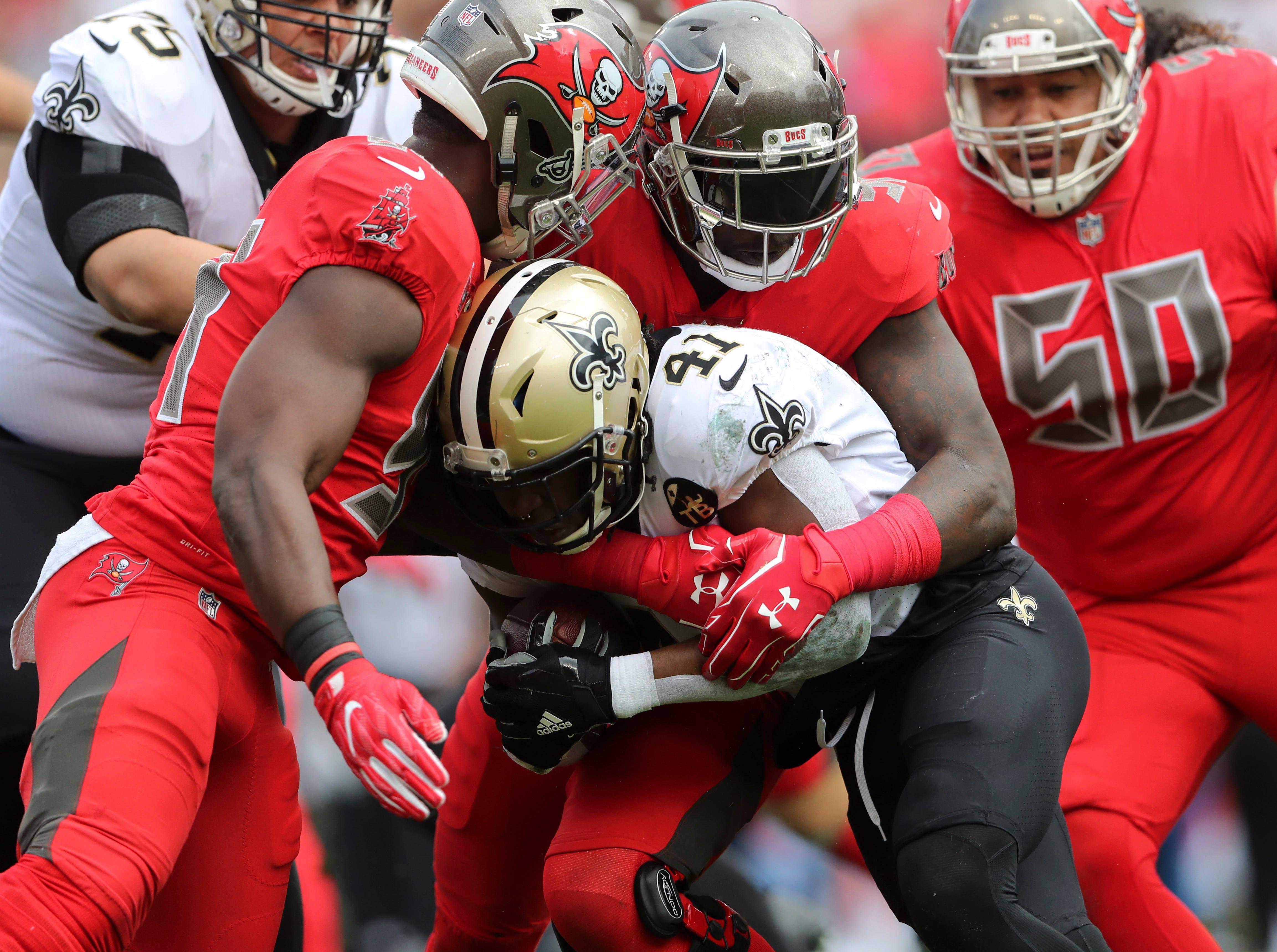 Saints running back Alvin Kamara is tackled against the Buccaneers.