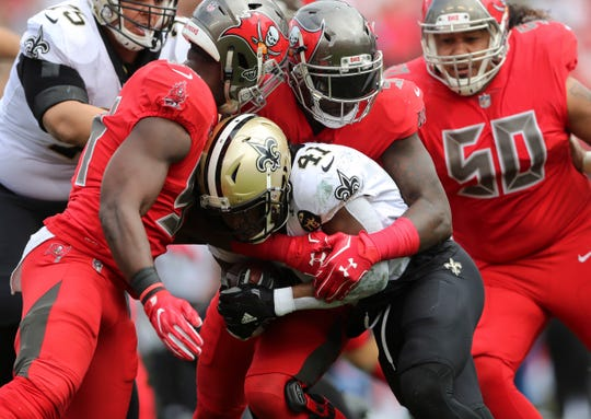 Saints running back Alvin Kamara is tackled against the Buccaneers.