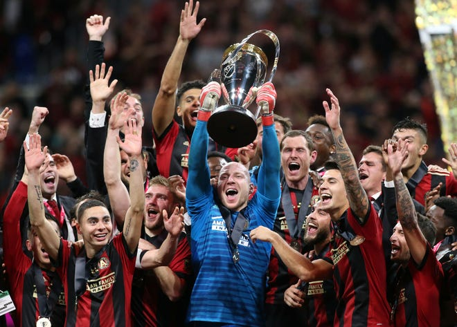 Atlanta United goalkeeper Brad Guzan lifts the MLS Cup as his teammates celebrate after their 2-0 win over the Portland Timbers in the Major League Soccer championshp game at Mercedes-Benz Stadium on Dec. 8.