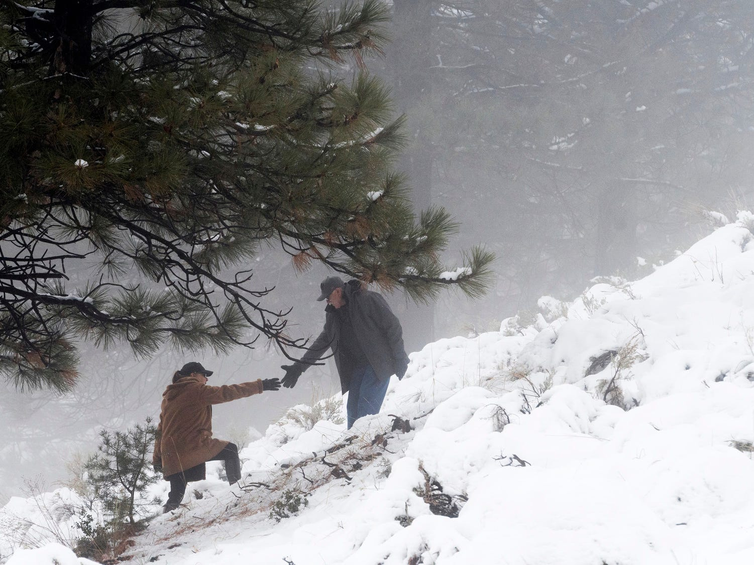 A hiker reaches out for help as visitors turned out to to play in the new coat of snow covering the mountains, Friday Dec. 7, 2018 in Wrightwood, Calif.