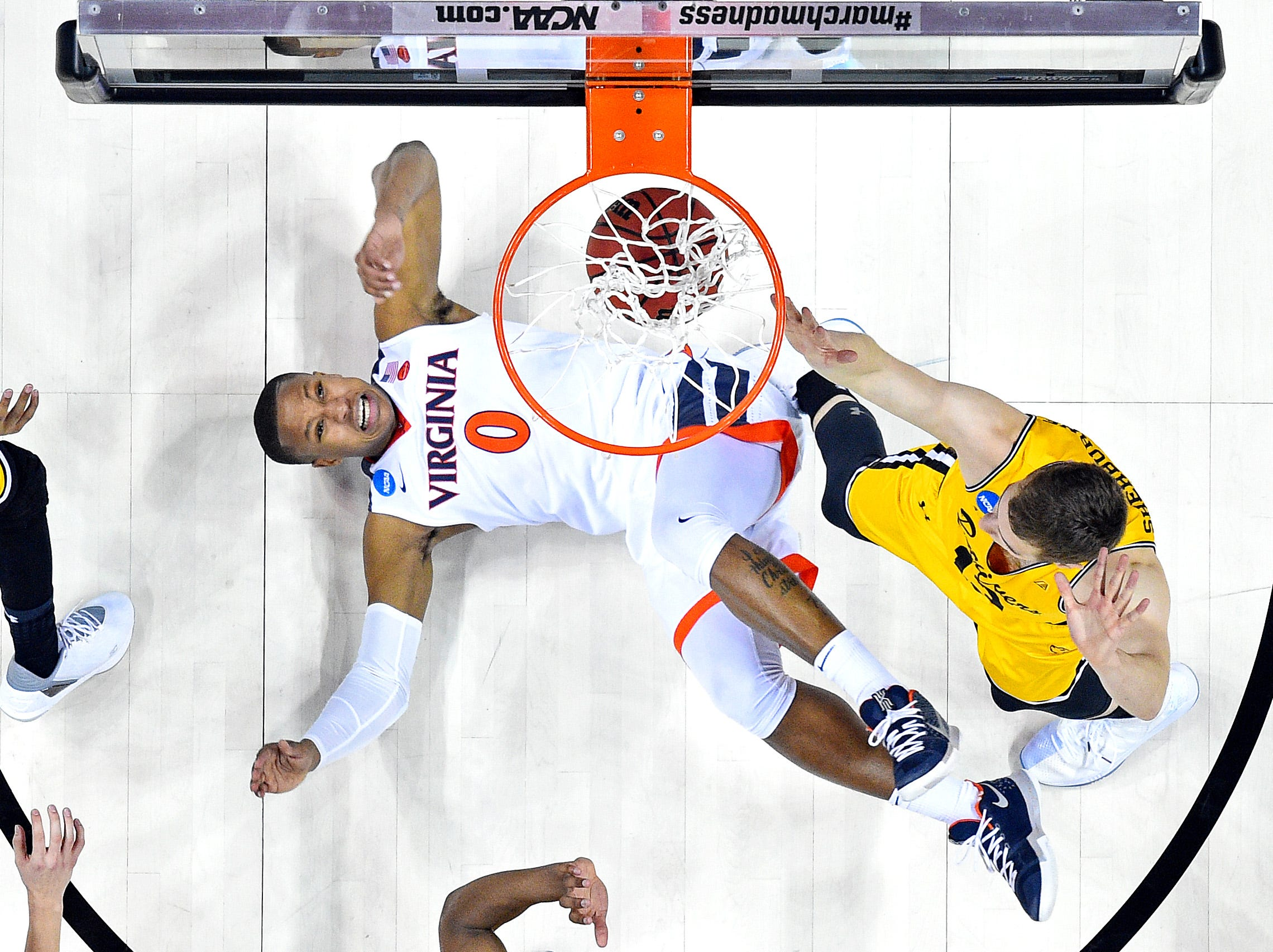 March 16: The Virginia Cavaliers' Devon Hall drives to the basket against UMBC Retrievers forward Joe Sherburne (13)  in the first round of the NCAA Tournament. UMBC became the first 16-seed to upset a No. 1.
