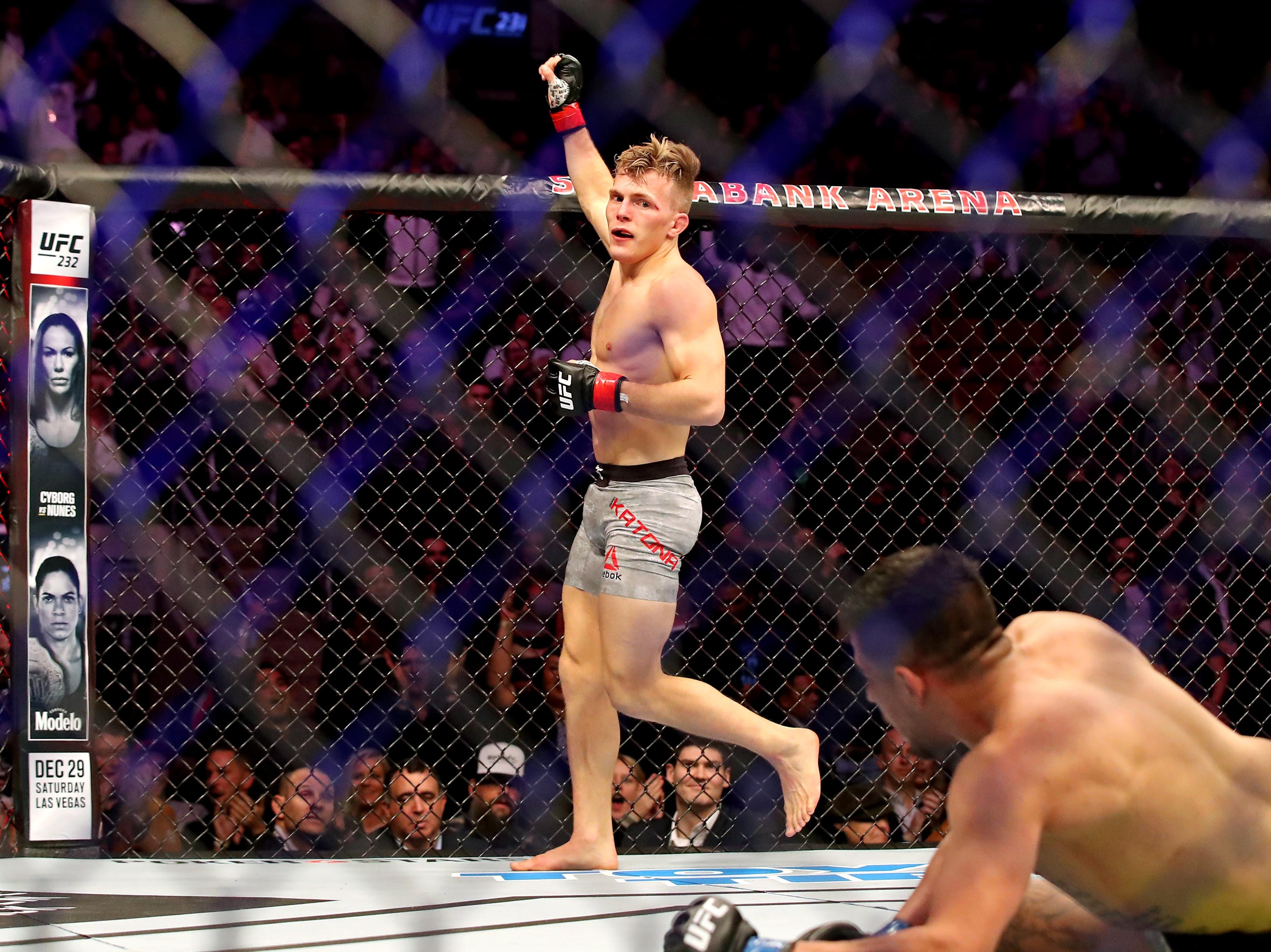 Brad Katona (red gloves) celebrates beating Matthew Lopez (blue gloves) during UFC 231 at Scotiabank Arena.