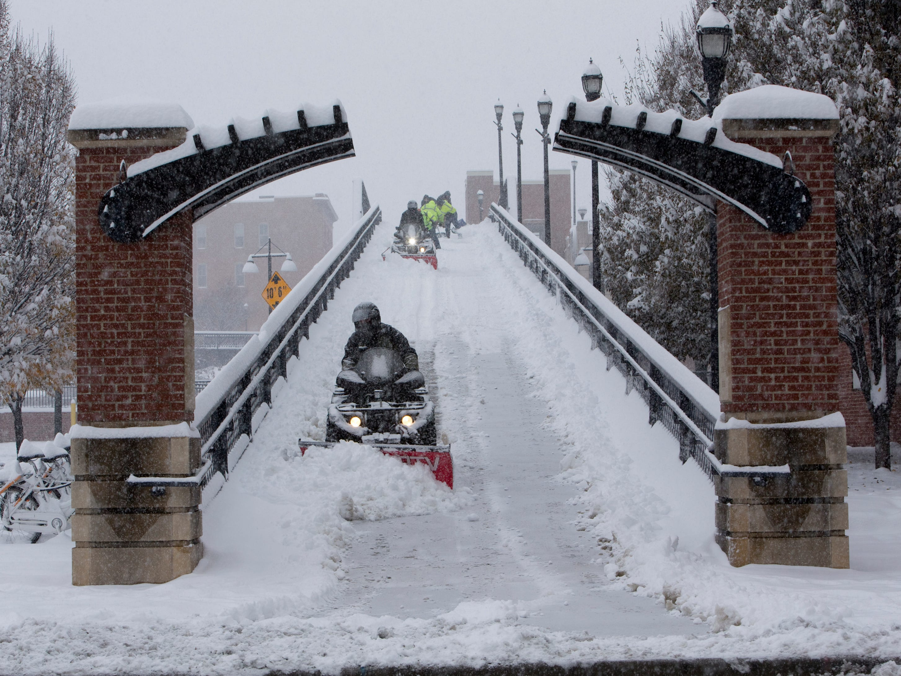 Workers plow and shovel the Martin Luther King Bridge at 1st Street and Salem Avenue in Roanoke, Va., Sunday, Dec. 9, 2018.
