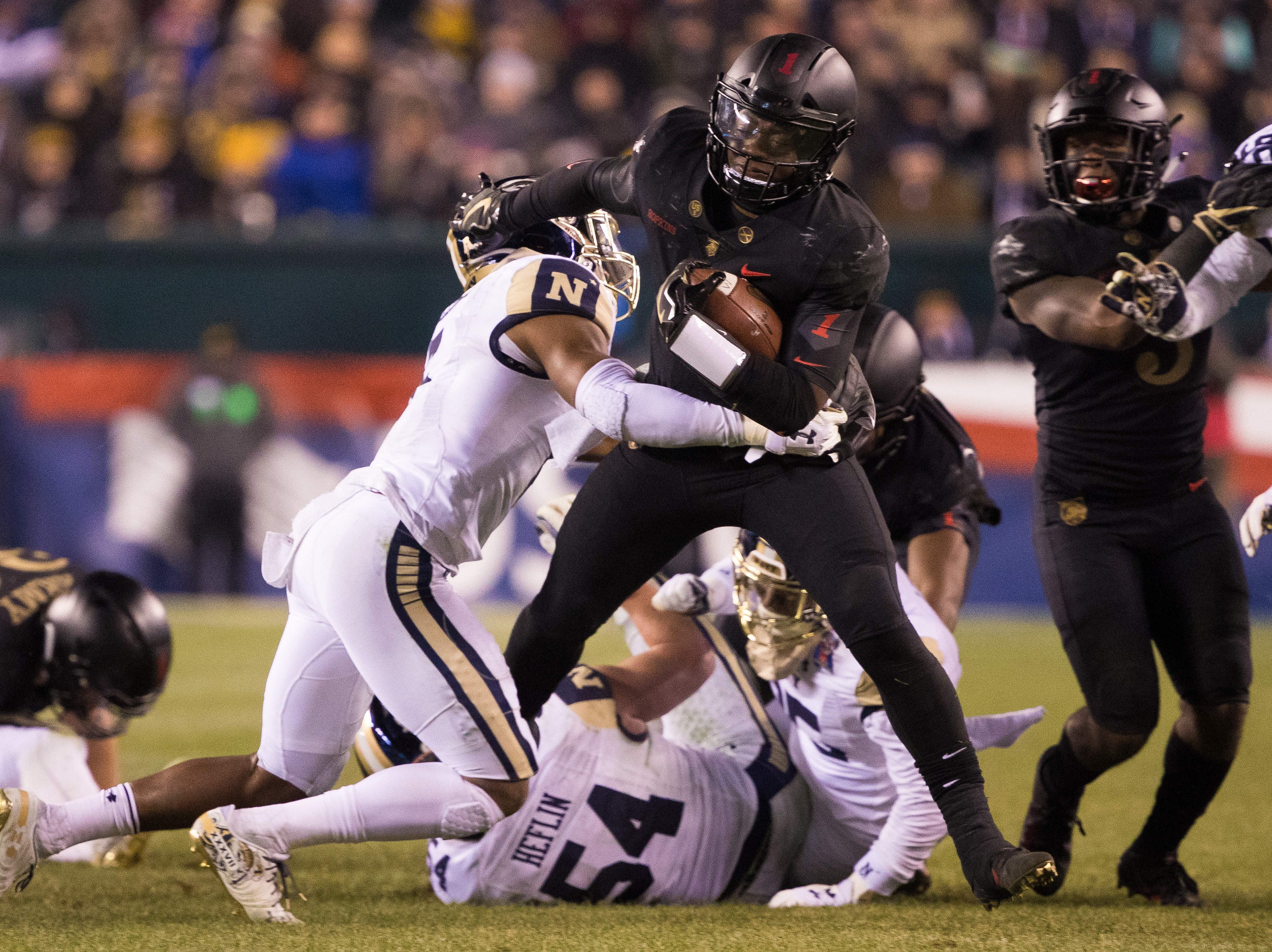Army Black Knights quarterback Kelvin Hopkins Jr. (8) runs for a first down past the tackle attempt of Navy Midshipmen defensive back Michael McMorris (5) at Lincoln Financial Field.