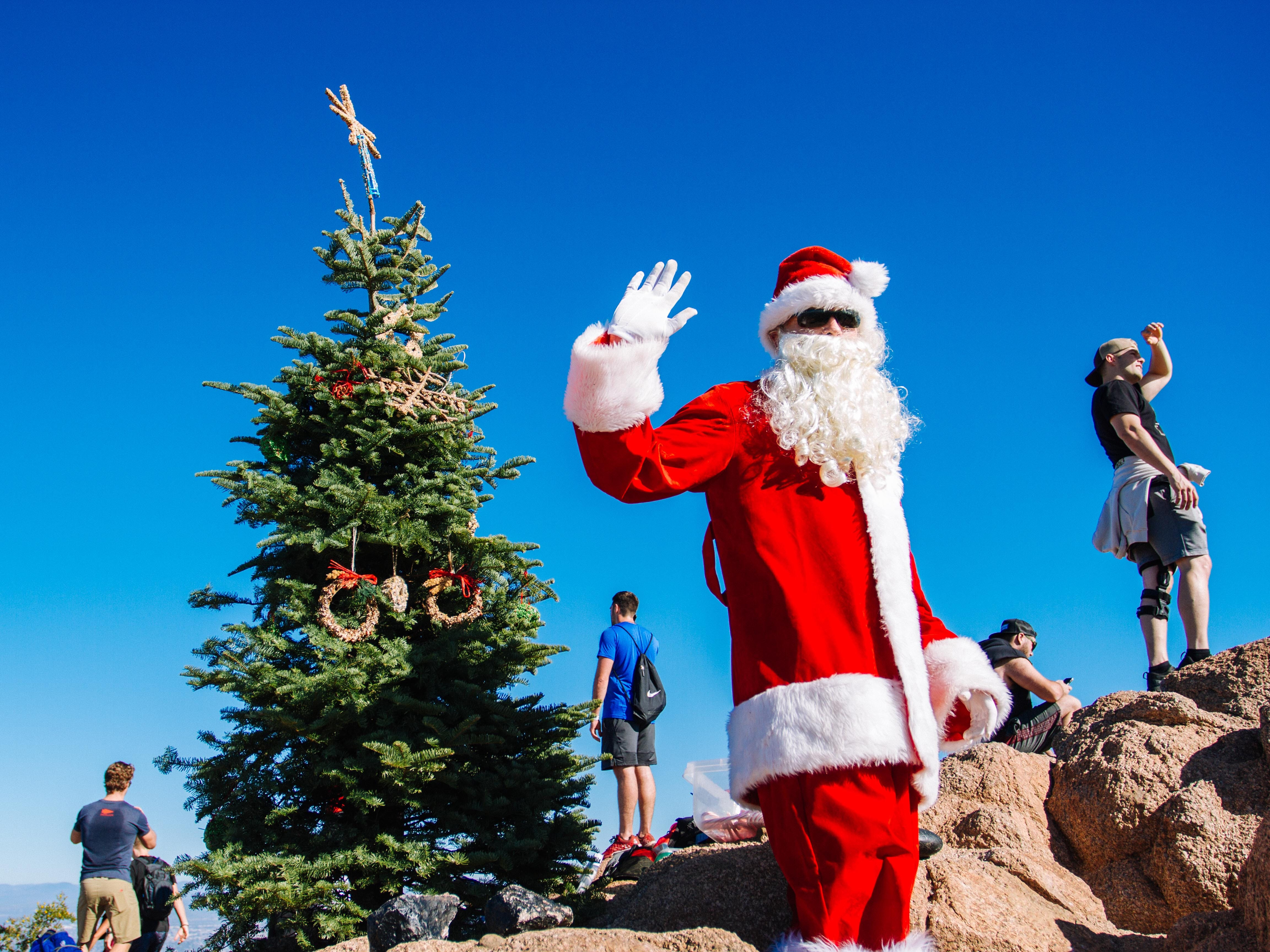 """John Cressey, the """"Camelback Santa,"""" poses with hikers at the top of Camelback Mountain in Phoenix, Ariz., Dec. 8, 2018."""