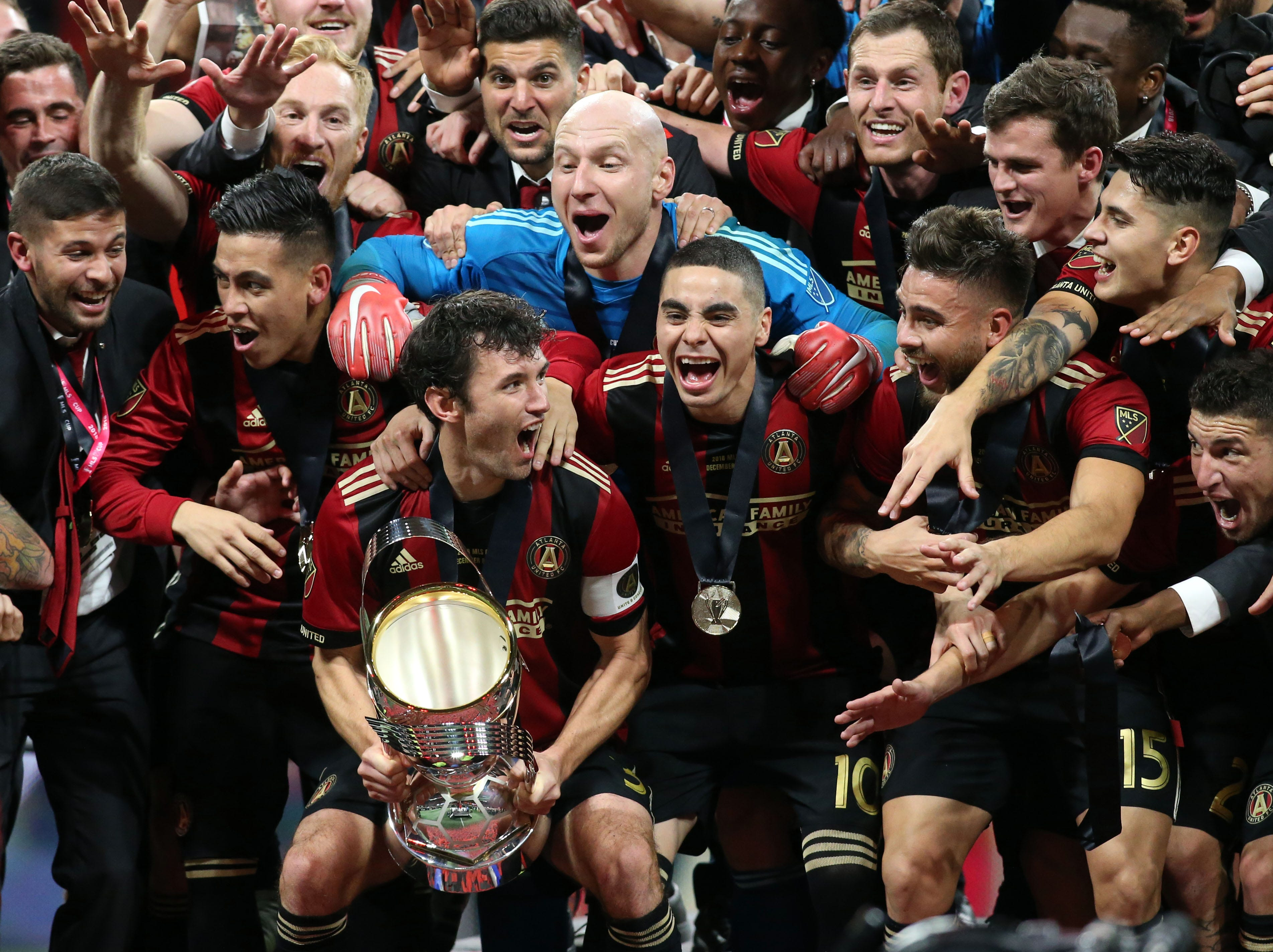 Atlanta United defender Michael Parkhurst holds the MLS Cup while celebrating with teammates after defeating the Portland Timbers 2-0 in the championship game at Mercedes-Benz Stadium.