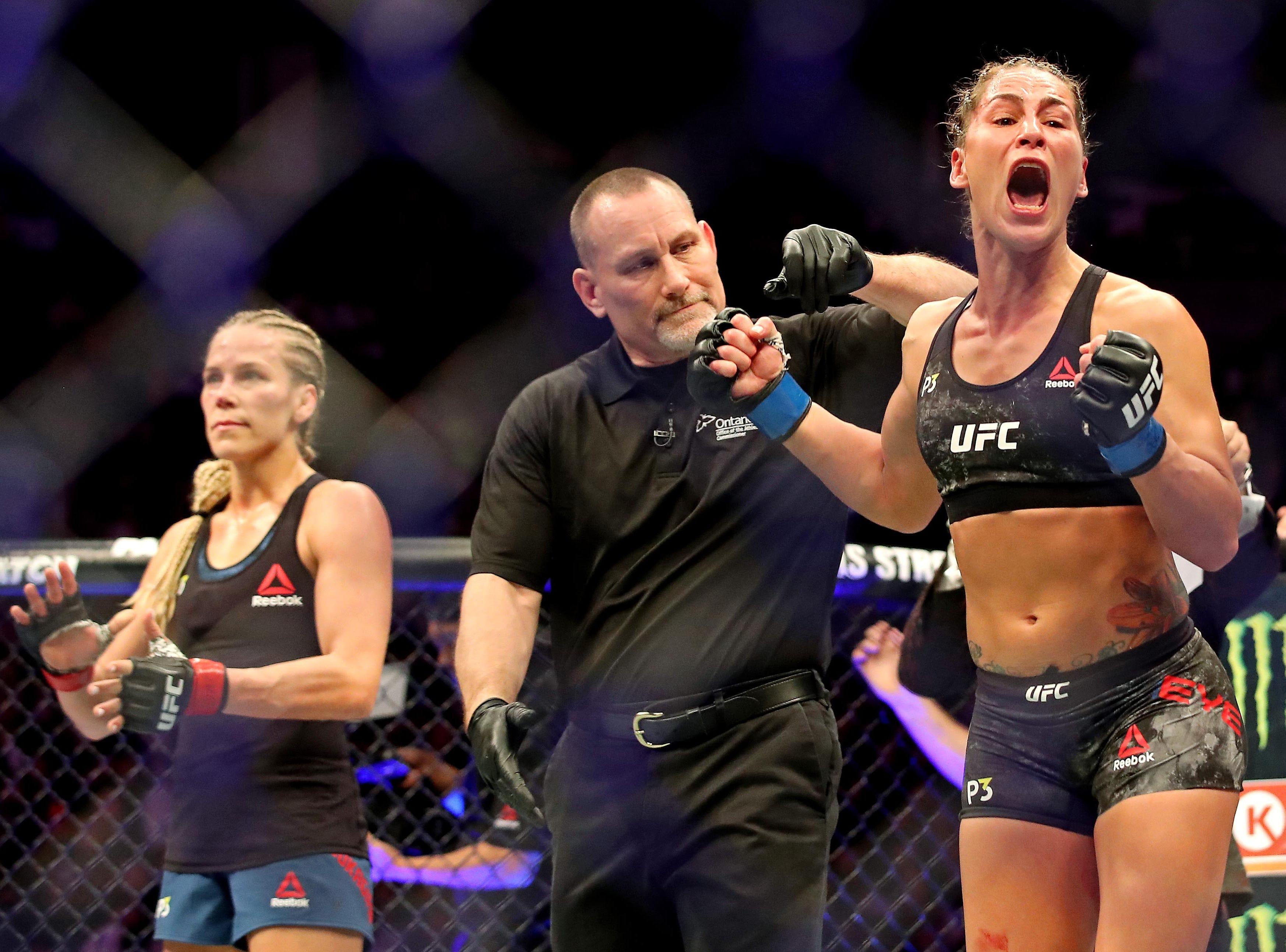 Jessica Eye (blue gloves) celebrates beating Katlyn Chookagian (red gloves) during UFC 231 at Scotiabank Arena.