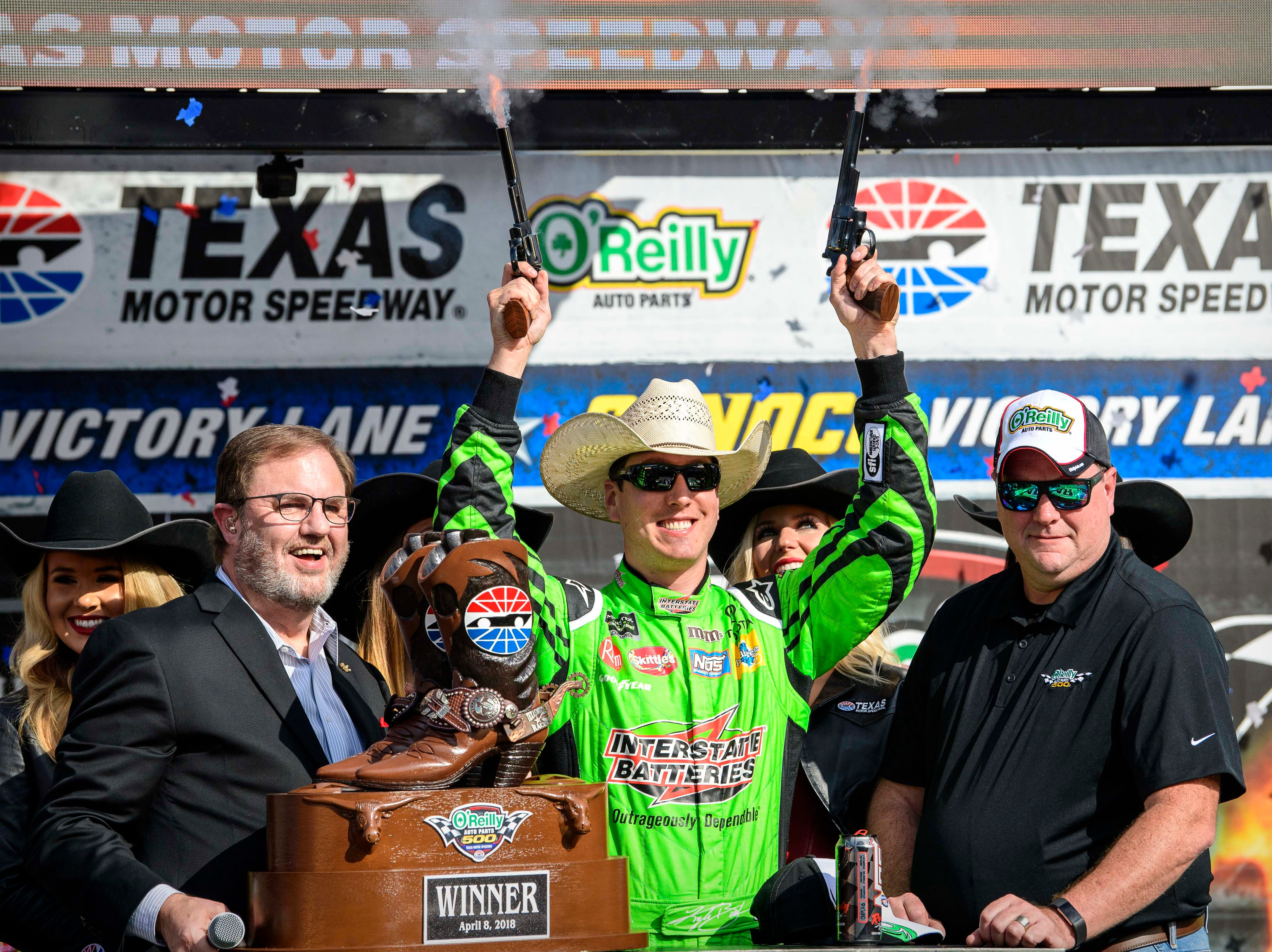 April 8: Kyle Busch fires off the six-shooter pistols after winning the O'Reilly Auto Parts 500 at Texas Motor Speedway.
