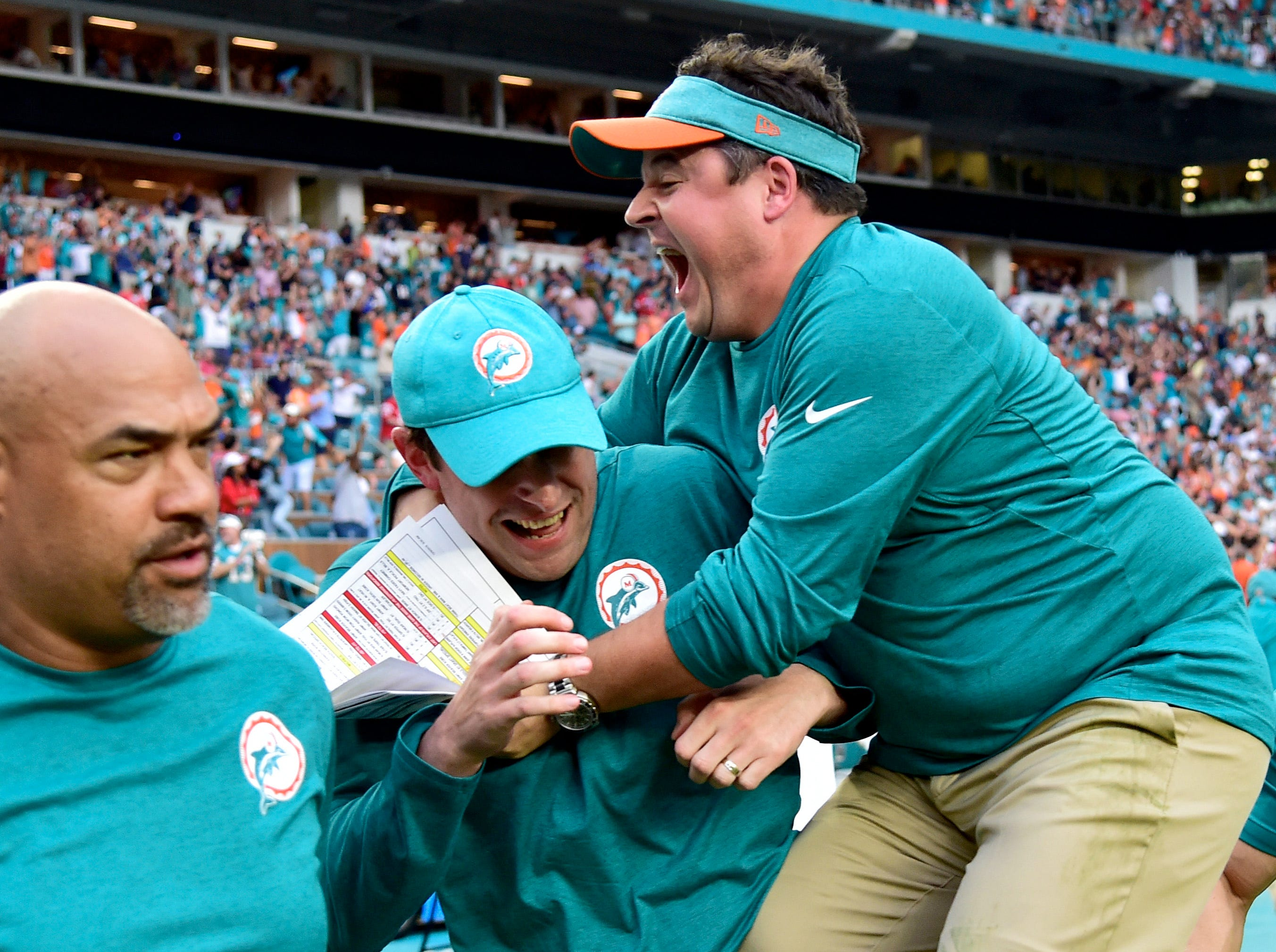 Dolphins coaches celebrate after the win against the Patriots.