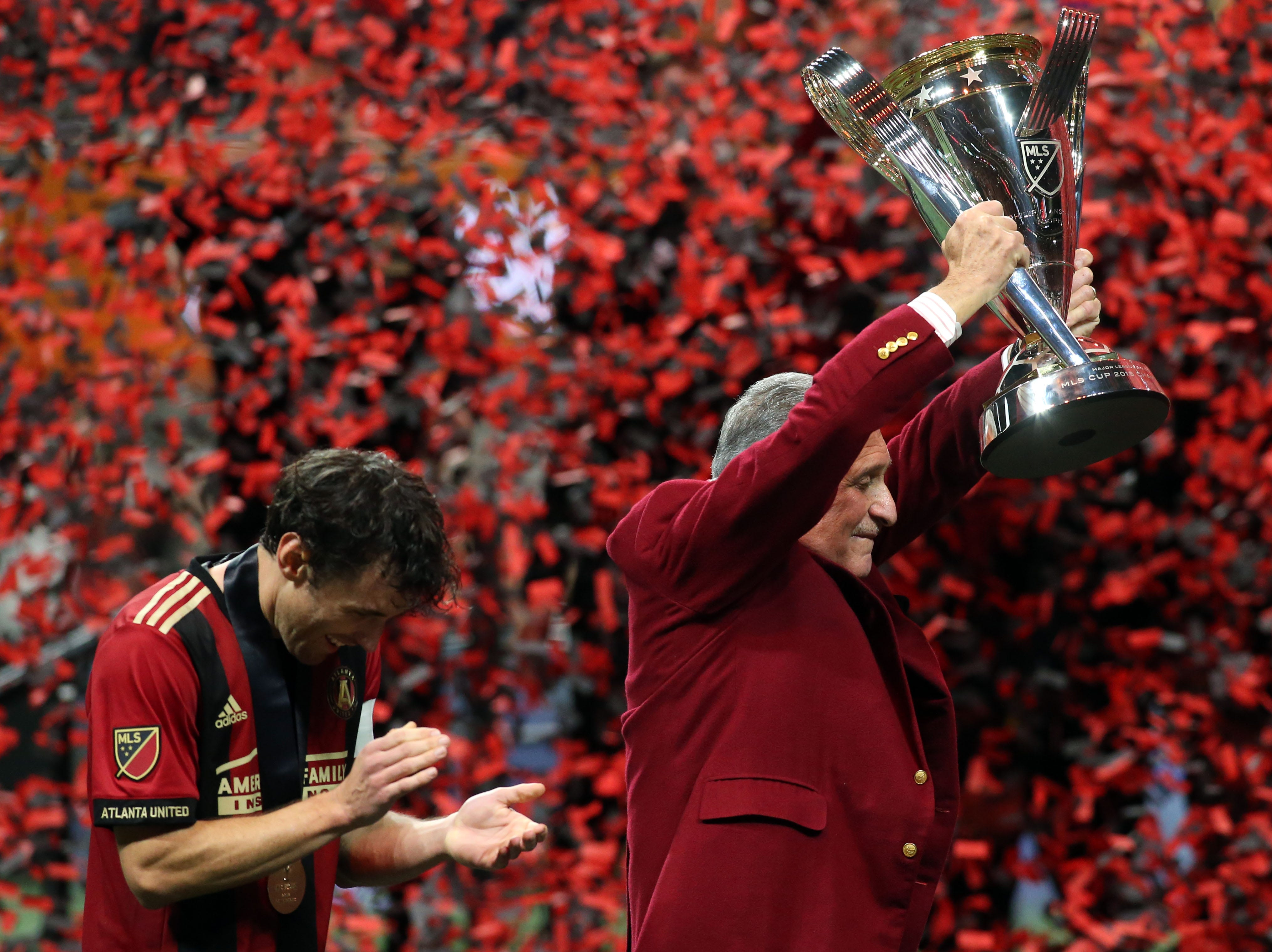 Atlanta United owner Arthur Blank raises MLS Cup next to defender Michael Parkhurst after the team won its first Major League Soccer championship.