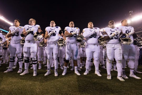 The Navy Midshipmen stand for their Alma Mater after a loss against the Army Black Knights at Lincoln Financial Field.