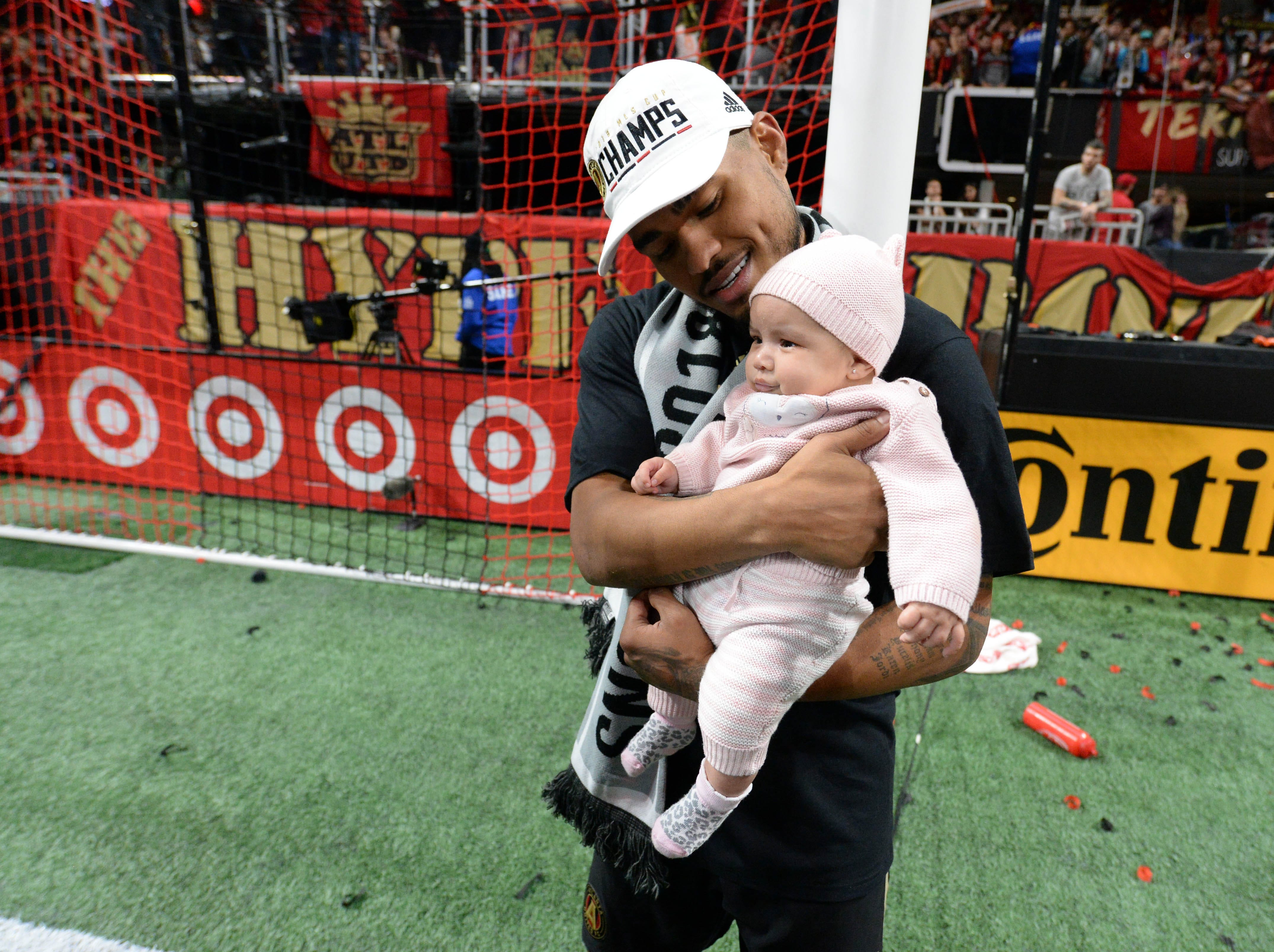Atlanta United forward Josef Martinez holds his baby after defeating the Portland Timbers in the 2018 MLS Cup.