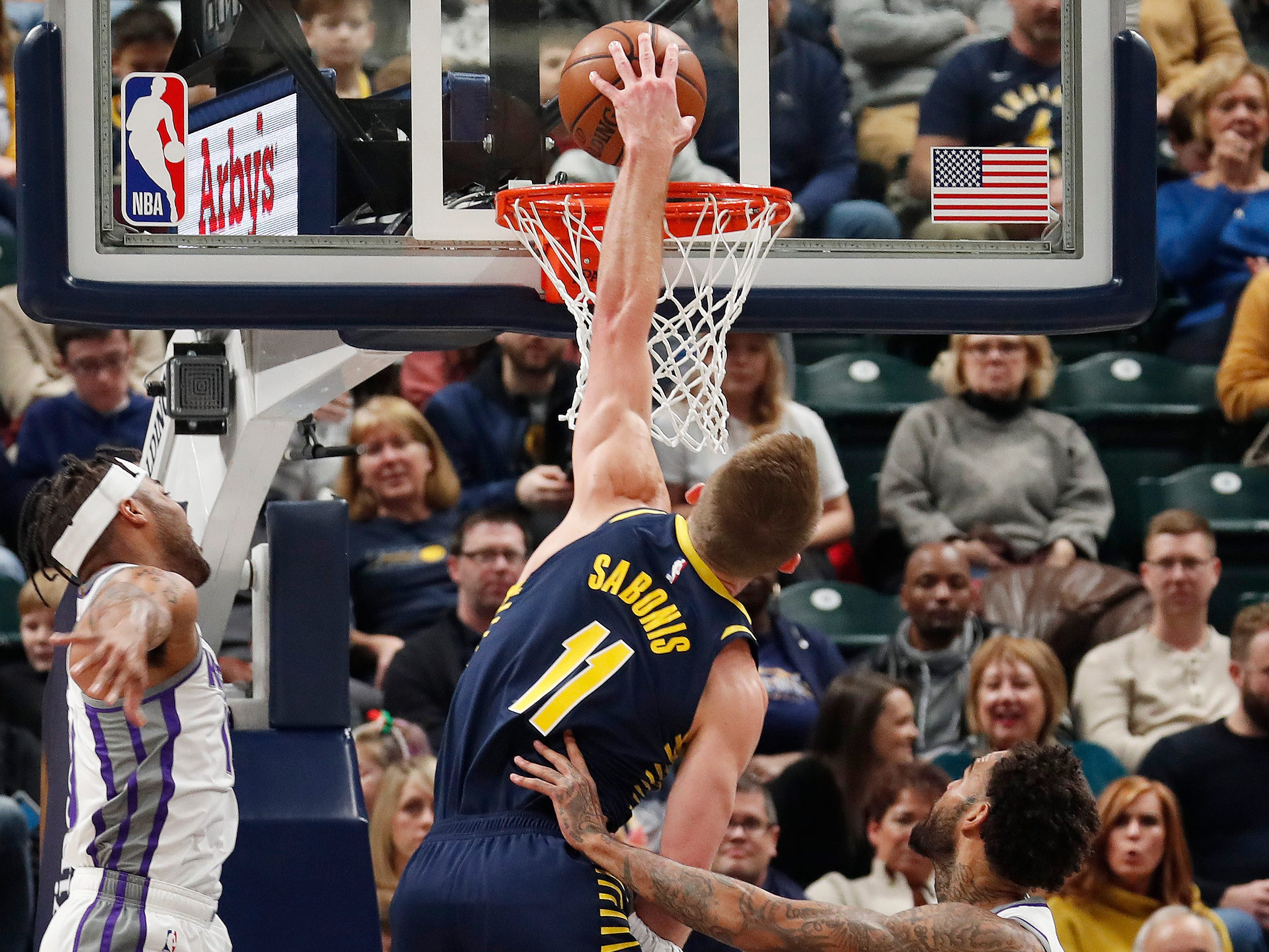 Dec. 8: Pacers forward Domantas Sabonis (11) throws down a ferocious one-handed slam between a pair of Kings defenders during the first half in Indianapolis.