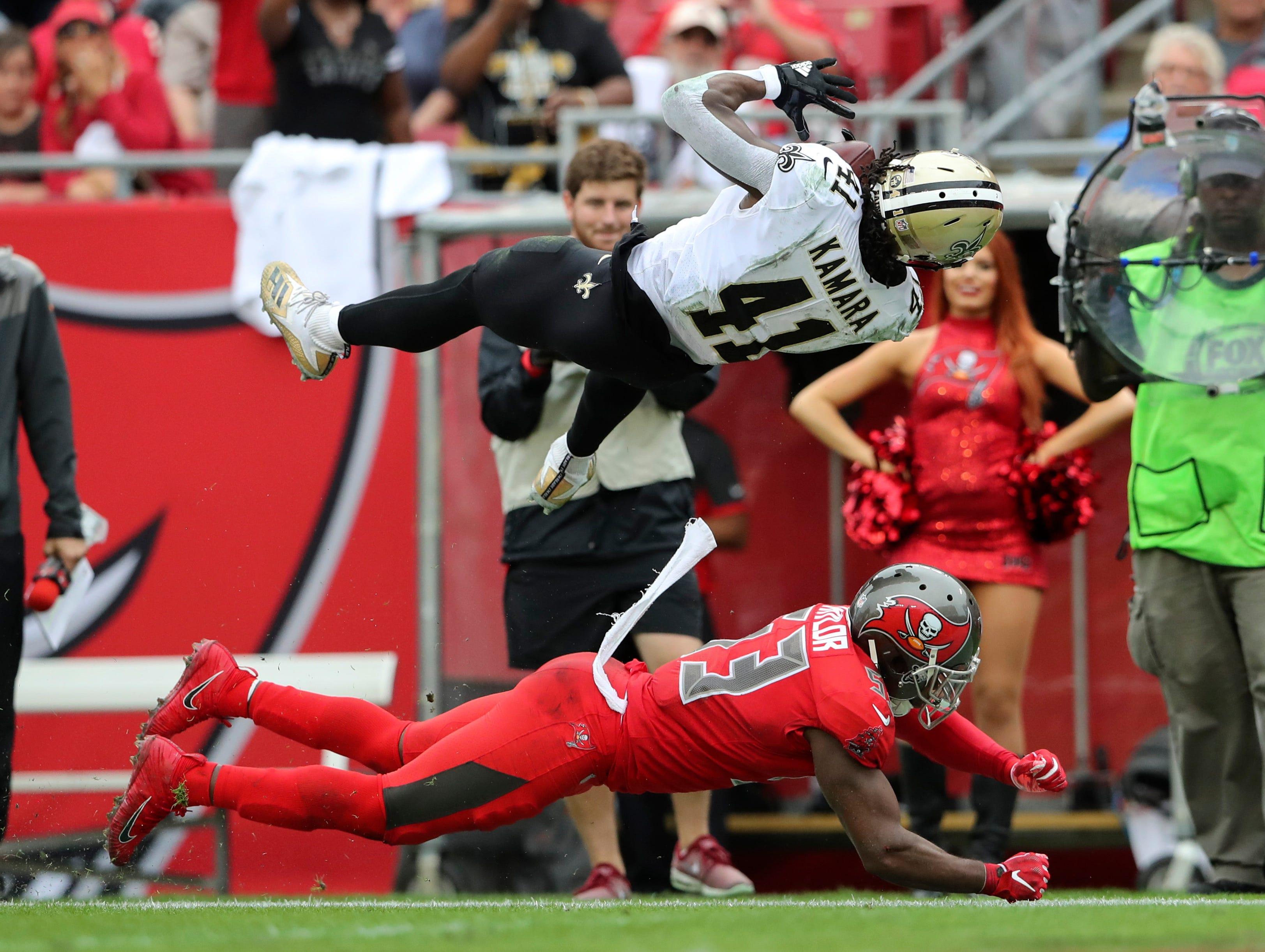 Saints running back Alvin Kamara leaps over Buccaneers outside linebacker Adarius Taylor during the second half.