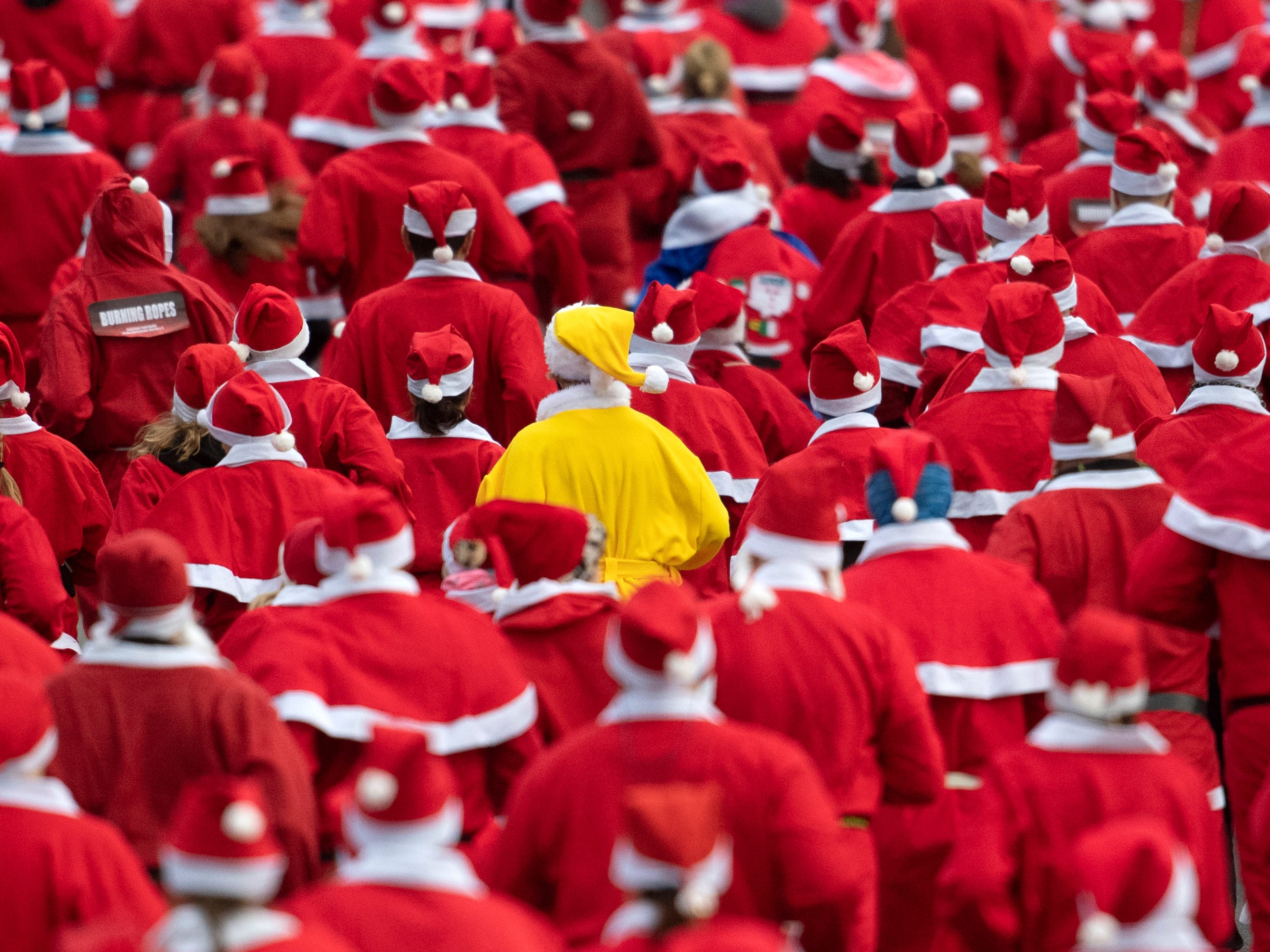 A runner wears a yellow costume during a Santa run with 1000 people in Michendorf, Germany, Sunday, Dec.9, 2018.