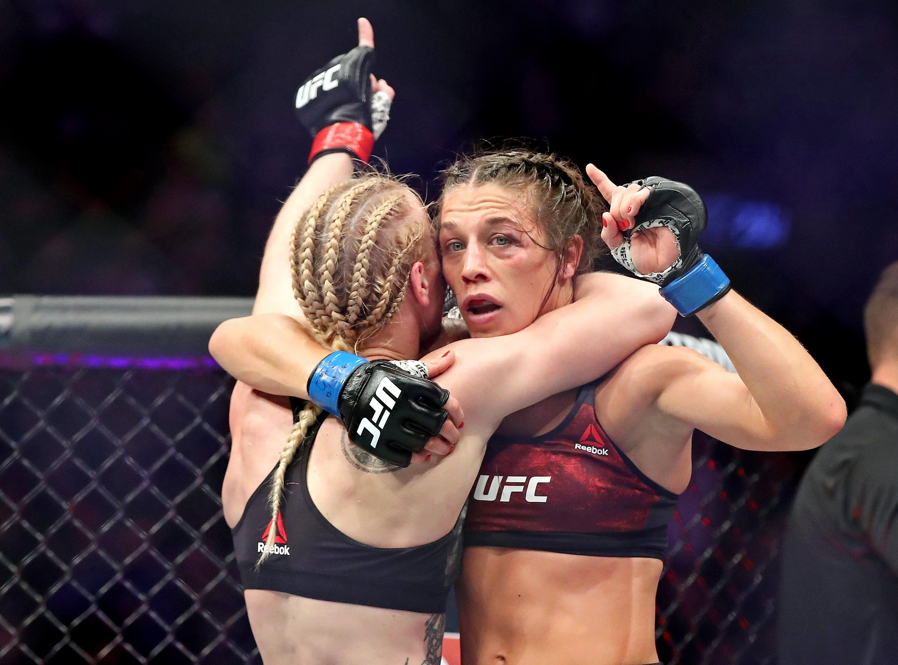 Valentina Shevchenko (red gloves) embraces Joanna Jedrzejczyk (blue gloves) after their fight during UFC 231 at Scotiabank Arena.