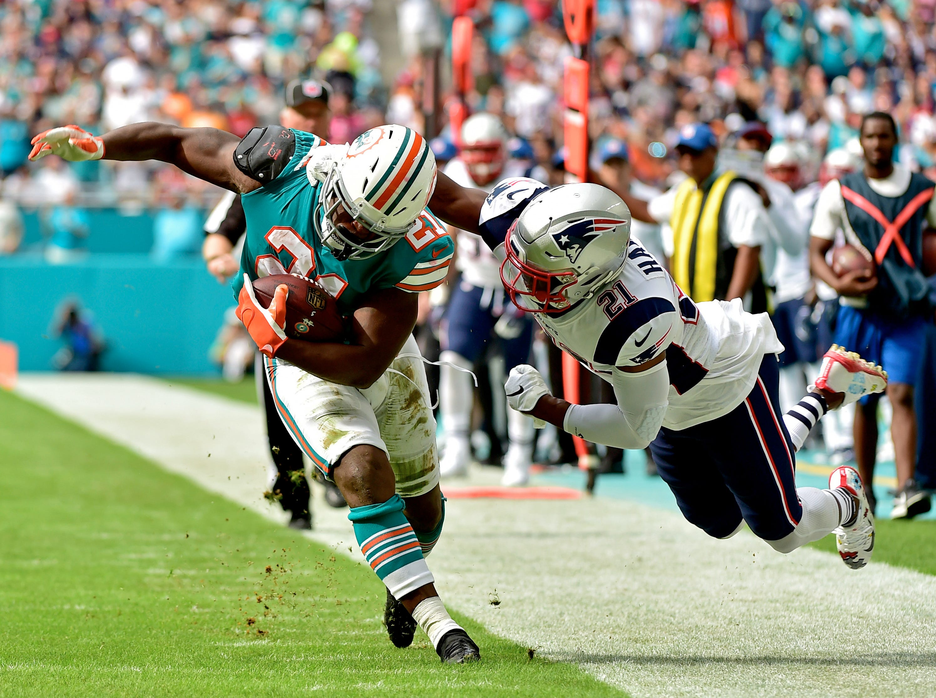 Patriots safety Duron Harmon tackles Dolphins running back Frank Gore during the first half.