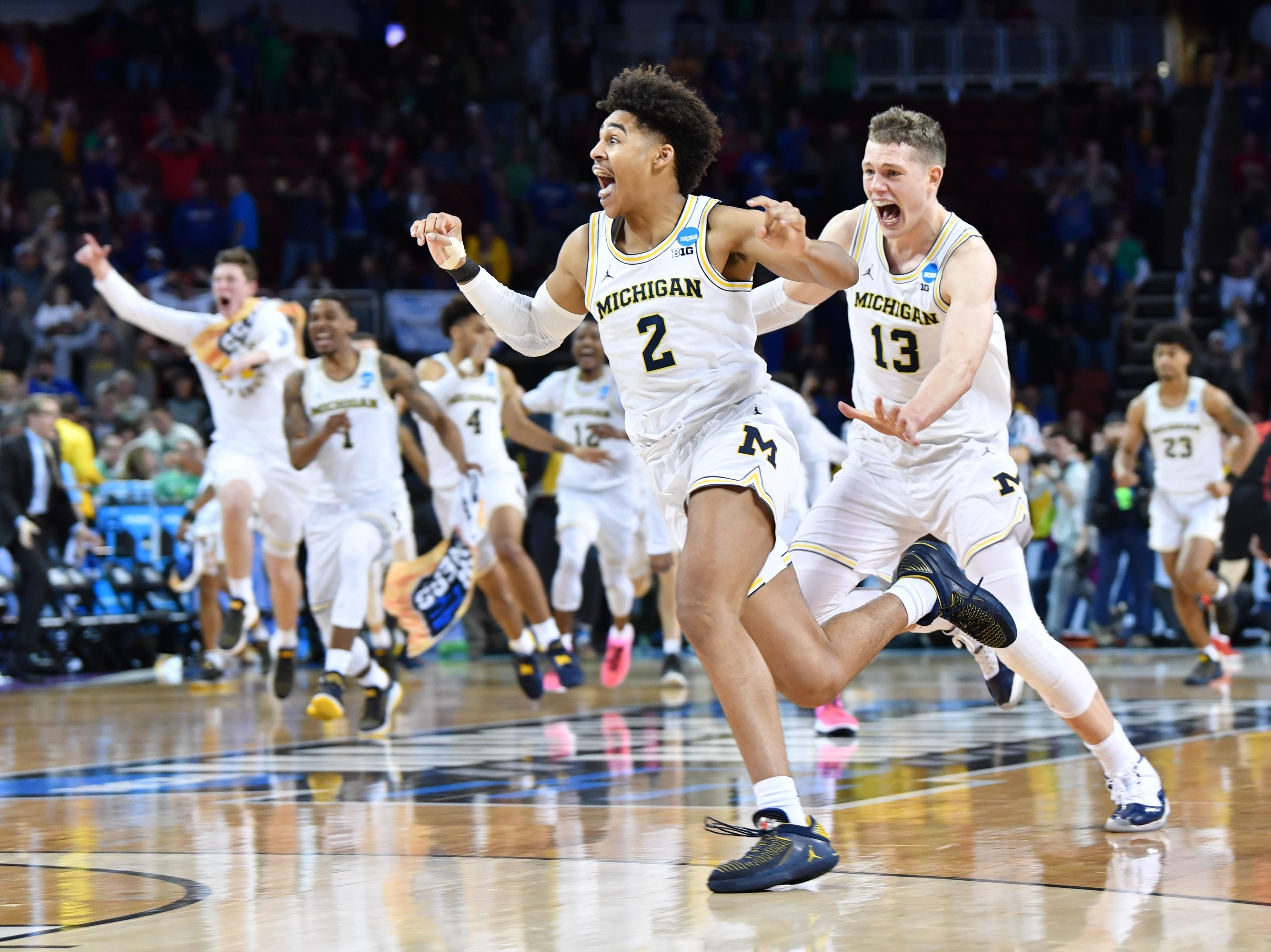 March 17: Michigan Wolverines guard Jordan Poole (2) celebrates with teammates after hitting the game-winning 3-pointer to defeat the Houston Cougars in the second round of the NCAA tournament.
