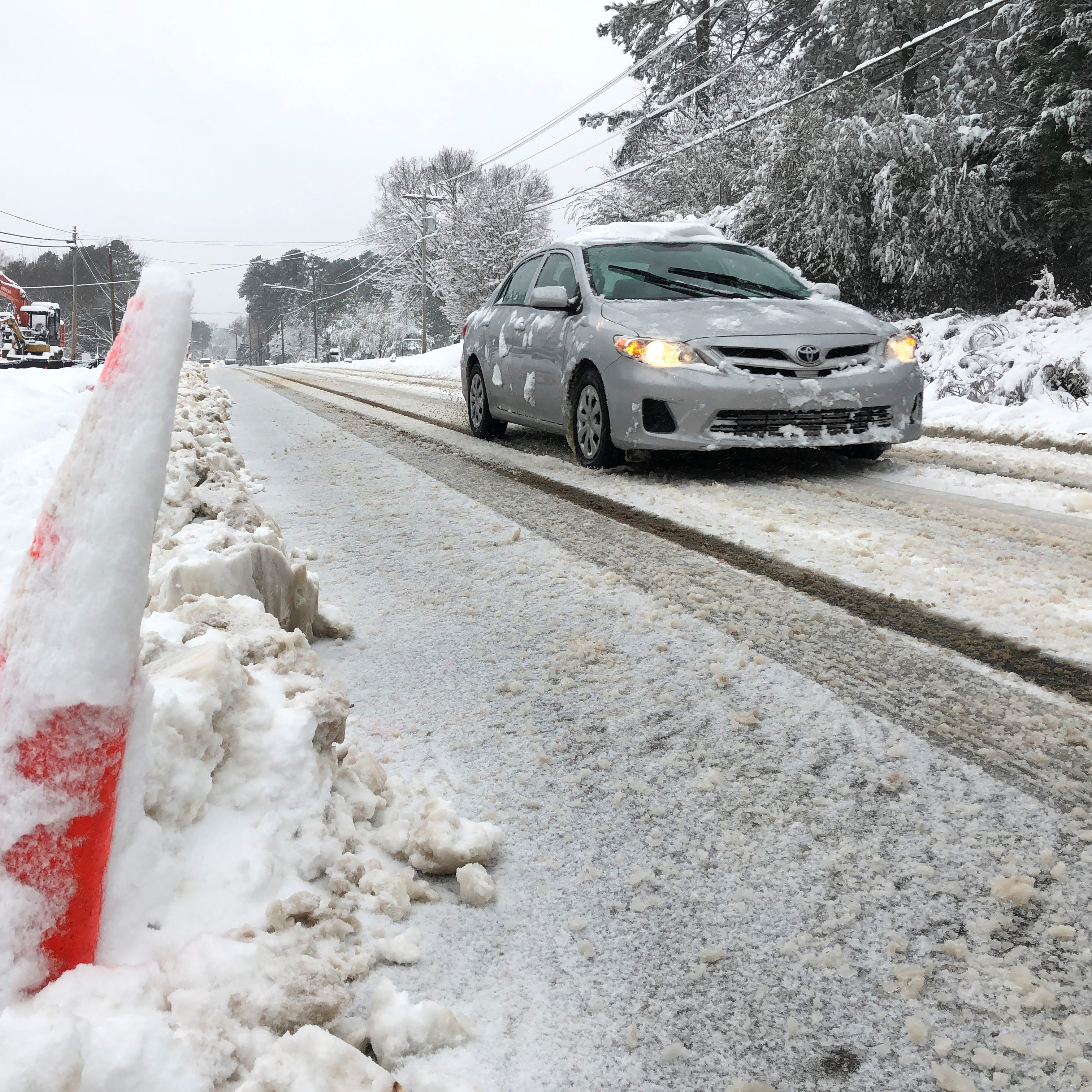 A car drives slowly down Old NC 98 in Wake Forest, N.C., on Sunday, Dec. 9, 2018. A storm spreading snow, sleet and freezing rain across a wide swath of the South has millions of people in its path, raising the threat of immobilizing snowfalls, icy roads and possible power outages.