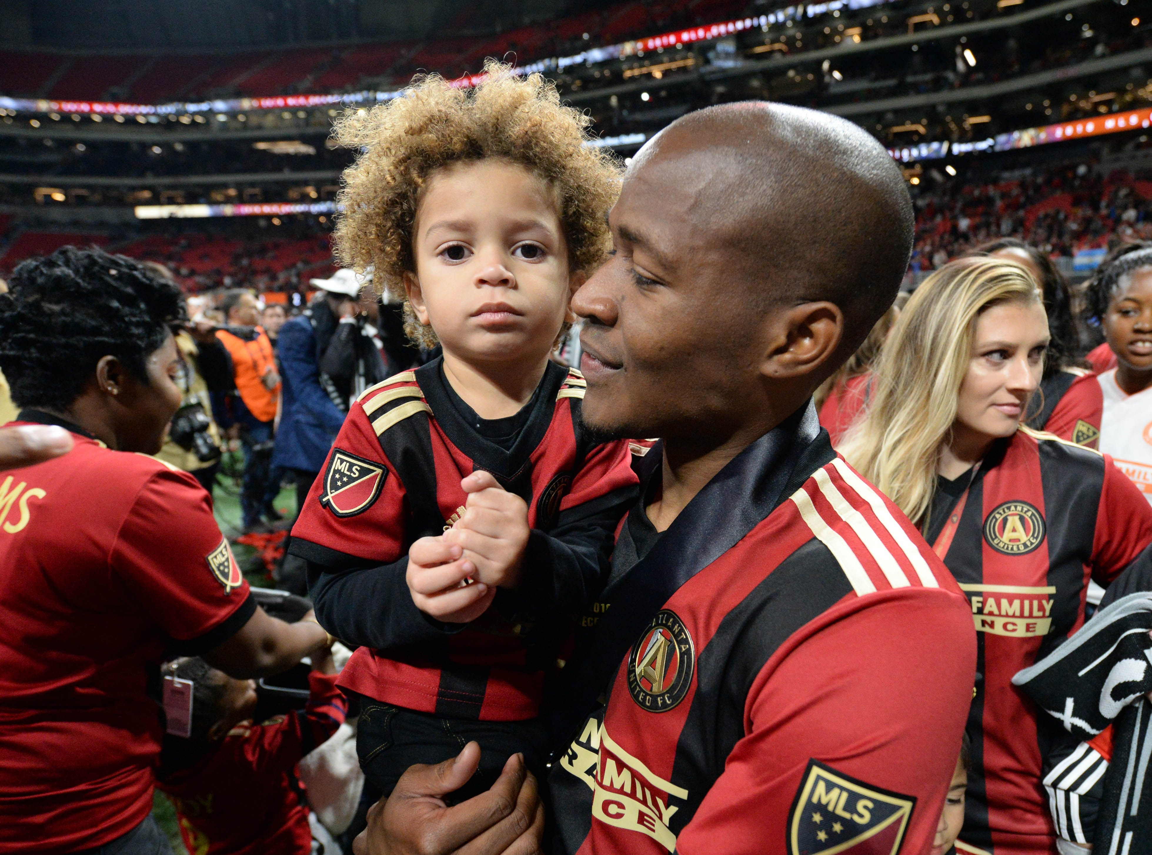 Atlanta United midfielder Darlington Nagbe celebrates with his child after defeating the Portland Timbers in the 2018 MLS Cup.