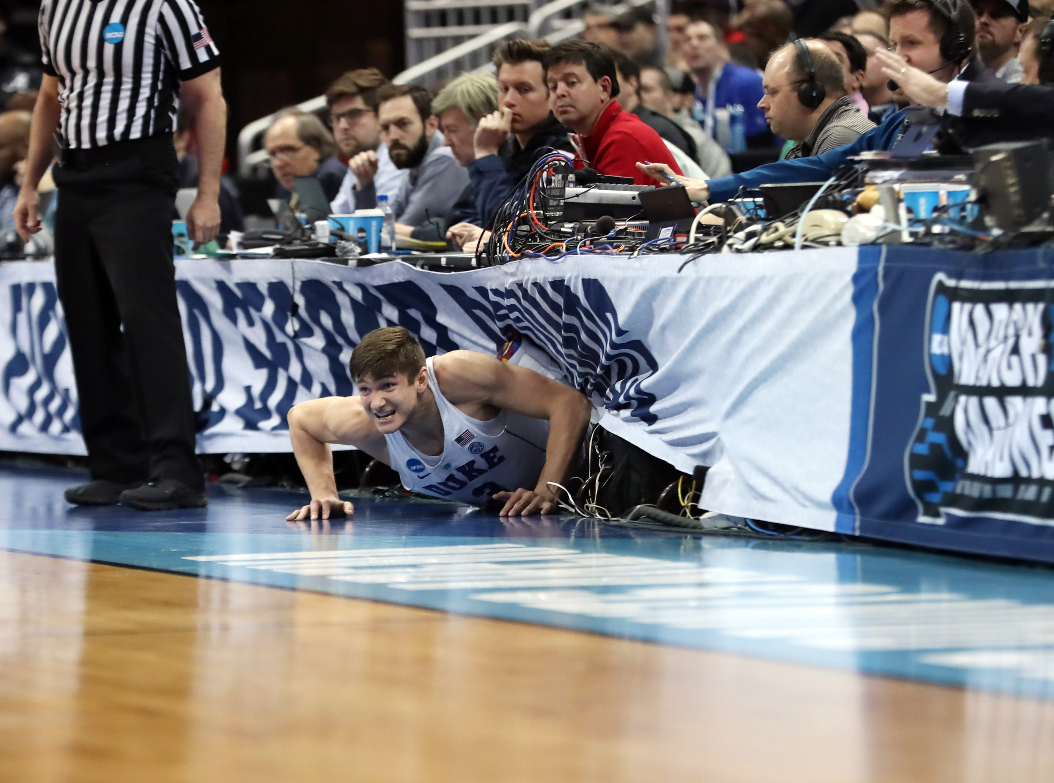 March 17: Duke Blue Devils guard Grayson Allen (3) slides into a table after attempting to save a ball against the Rhode Island Rams during the second round of the NCAA tournament.