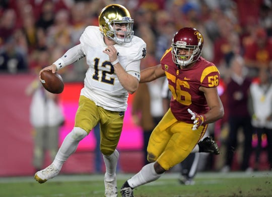 Nov 24, 2018; Los Angeles, CA, USA; Notre Dame Fighting Irish quarterback Ian Book (12) is pressured by Southern California Trojans linebacker Jordan Iosefa (56) in the second quarter at Los Angeles Memorial Coliseum. Mandatory Credit: Kirby Lee-USA TODAY Sports