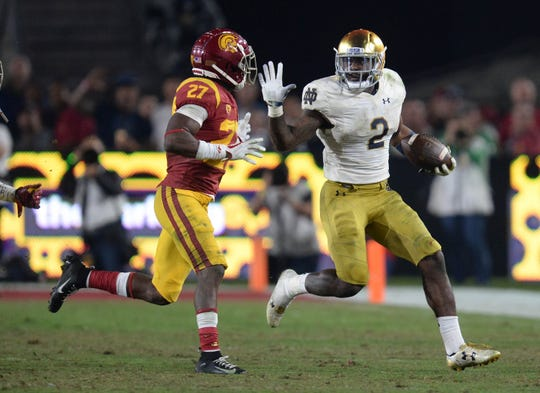 November 24, 2018; Los Angeles, CA, USA; Notre Dame Fighting Irish running back Dexter Williams (2) runs the ball against Southern California Trojans cornerback Ajene Harris (27) during the second half at the Los Angeles Memorial Coliseum. Mandatory Credit: Gary A. Vasquez-USA TODAY Sports
