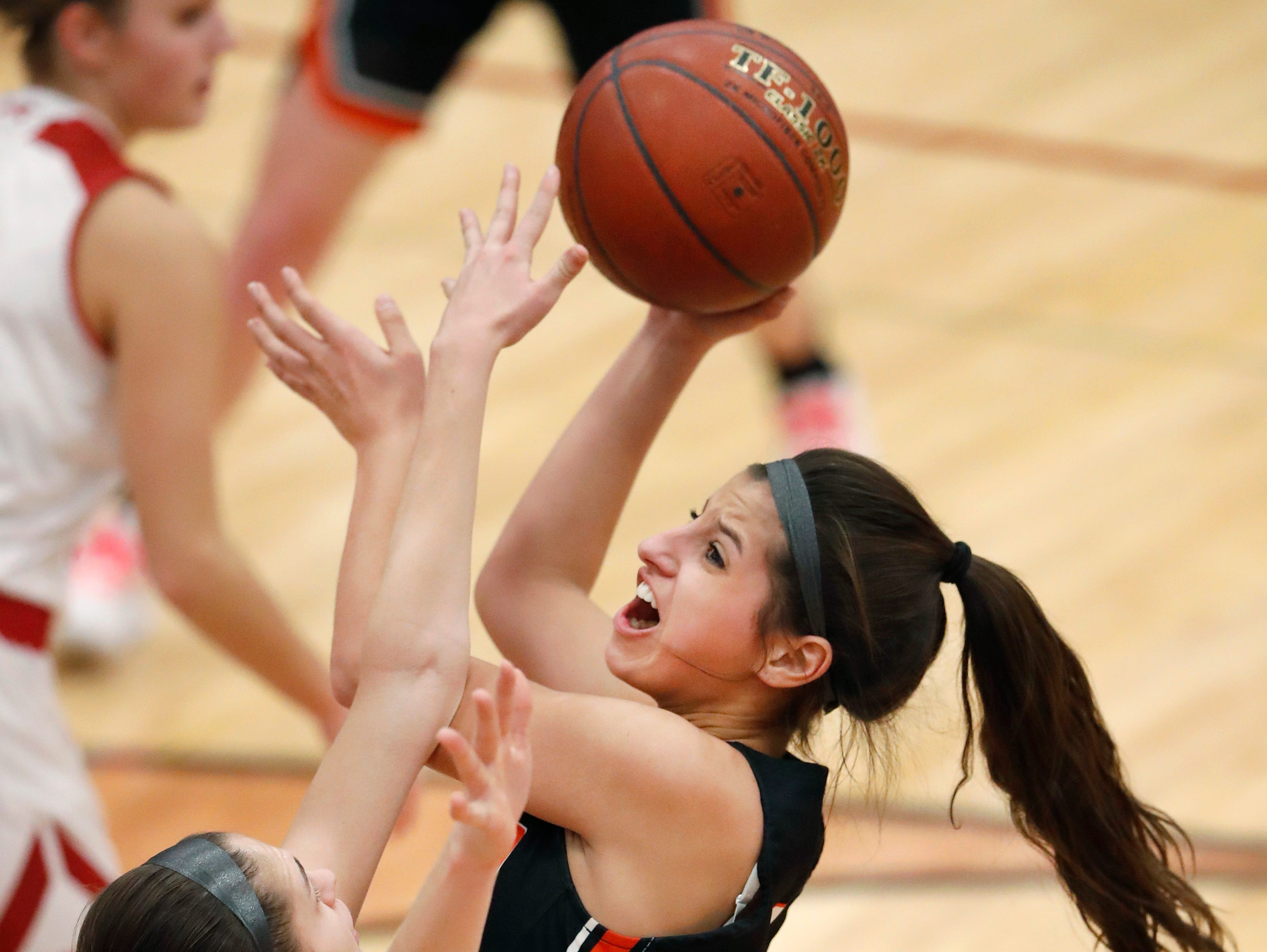 Kimberly High School's Bryn Sikora tries to block a shot from Kaukauna High School's Sutten Ebben Friday, Dec. 7, 2018, in Kimberly, Wis. Kimberly High School defeated Kaukauna High School 70-55.