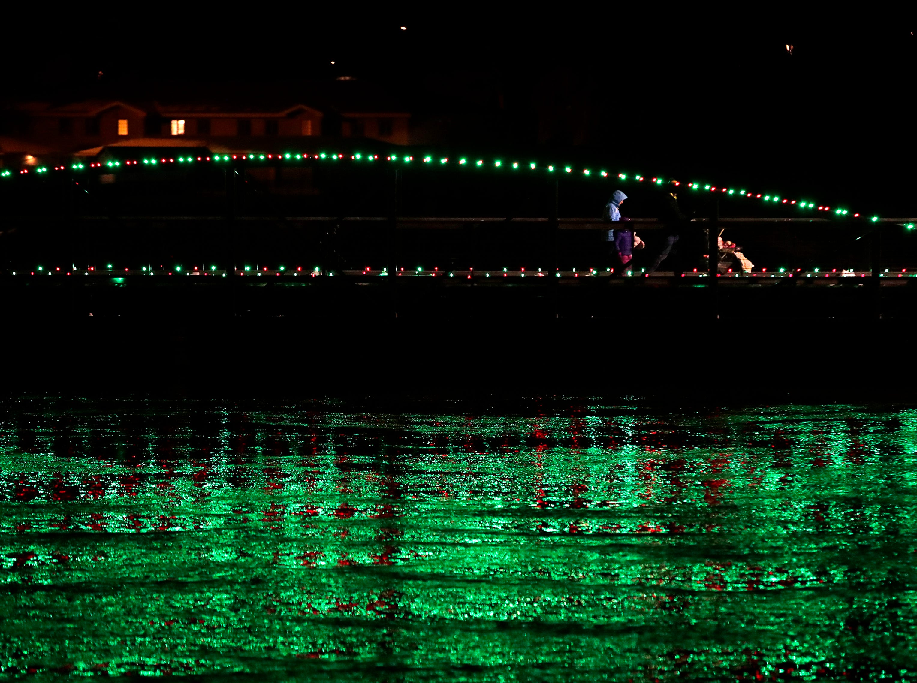 A family crosses a bridge over the Fox River during the Electric City Christmas Parade Tuesday, Dec. 4, 2018, in Kaukauna, Wis.
