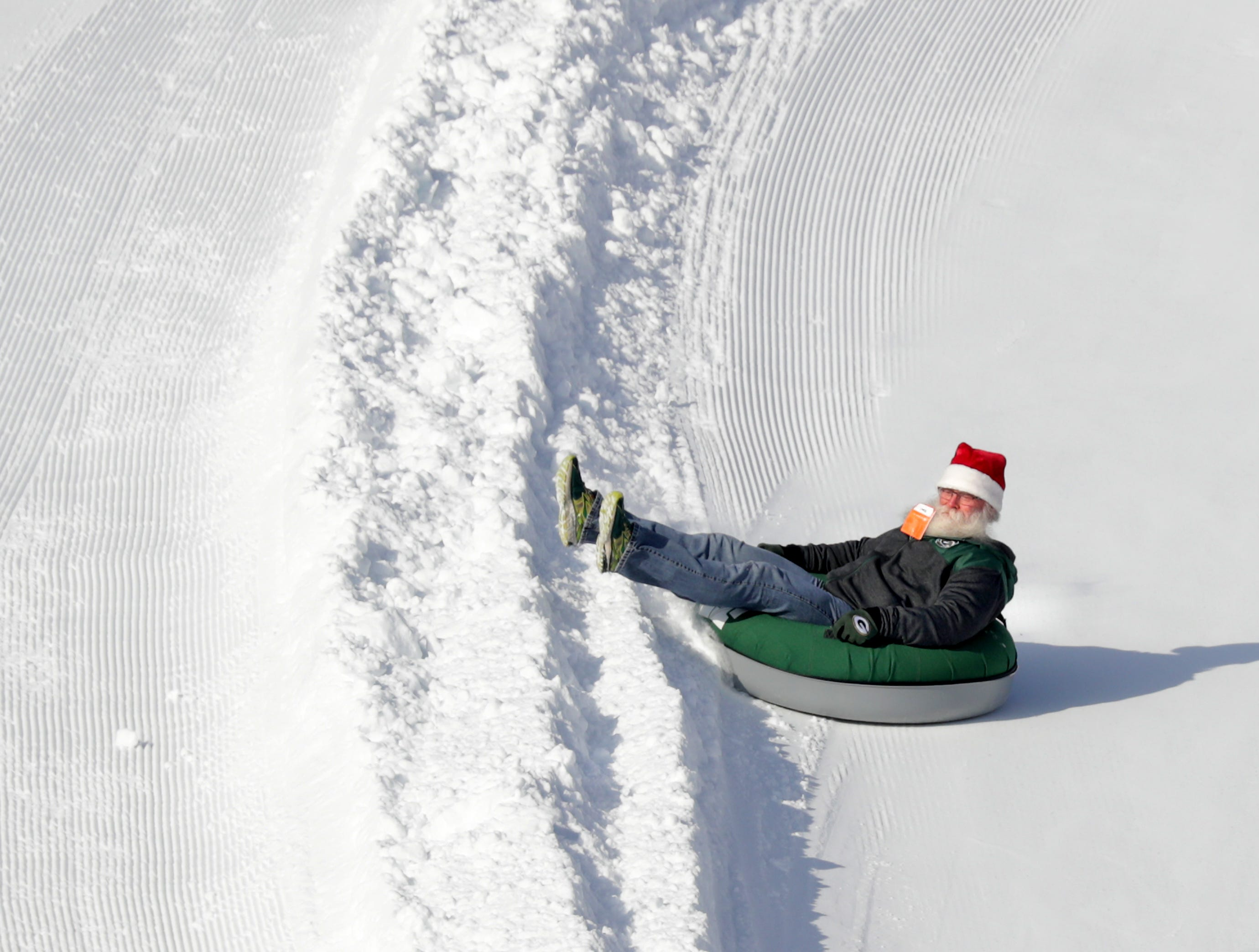 A Packers fan with a resemblance to Santa, slides down a sledding hill in the Titletown District before the Green Bay Packers take on the Atlanta Falcons during their football game on Sunday, December 9, 2018, at Lambeau Field in Green Bay, Wis.