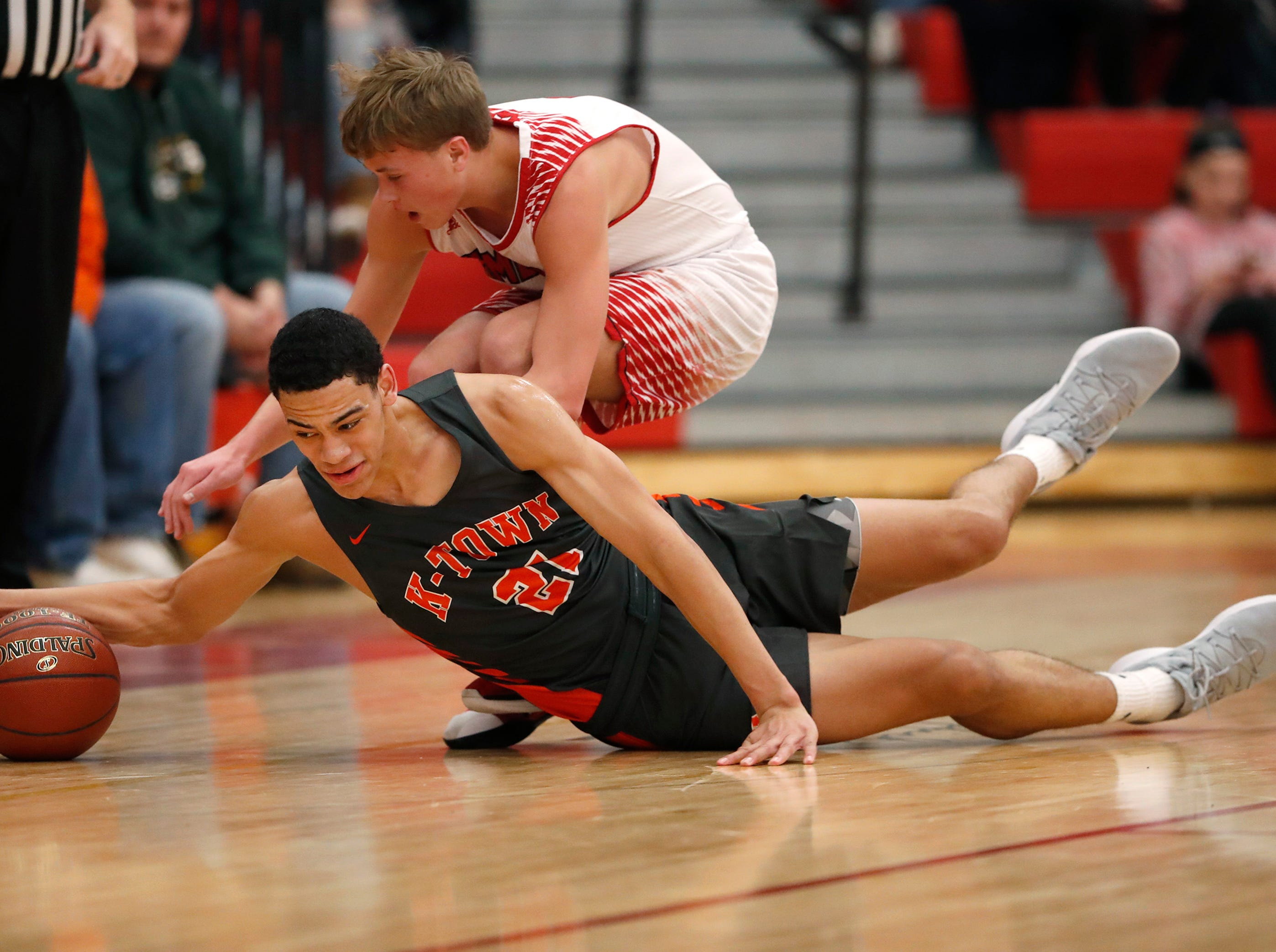 Kaukauna High School's Donovan Ivory and Kimberly High School's Jake Buchanan trip over each other as they chase after the ball Friday, Dec. 7, 2018, in Kimberly, Wis.